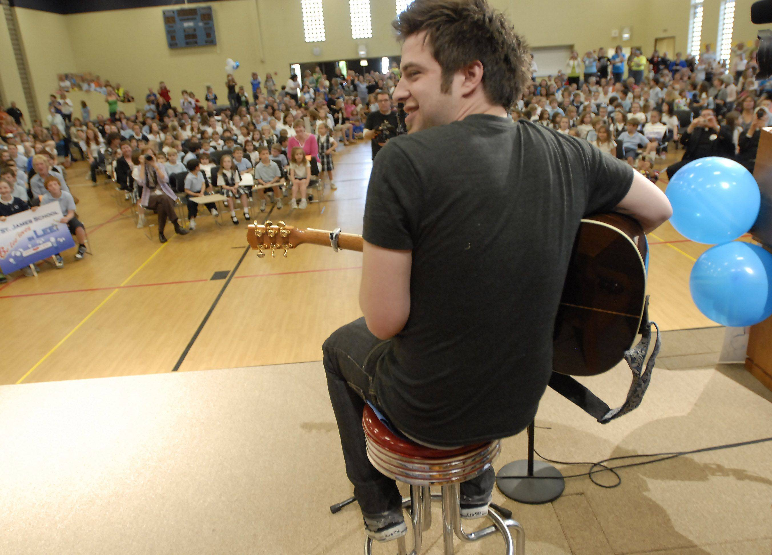 Lee DeWyze laughs when the bell goes off as he begins singing at St. James Catholic School in Arlington Heights.