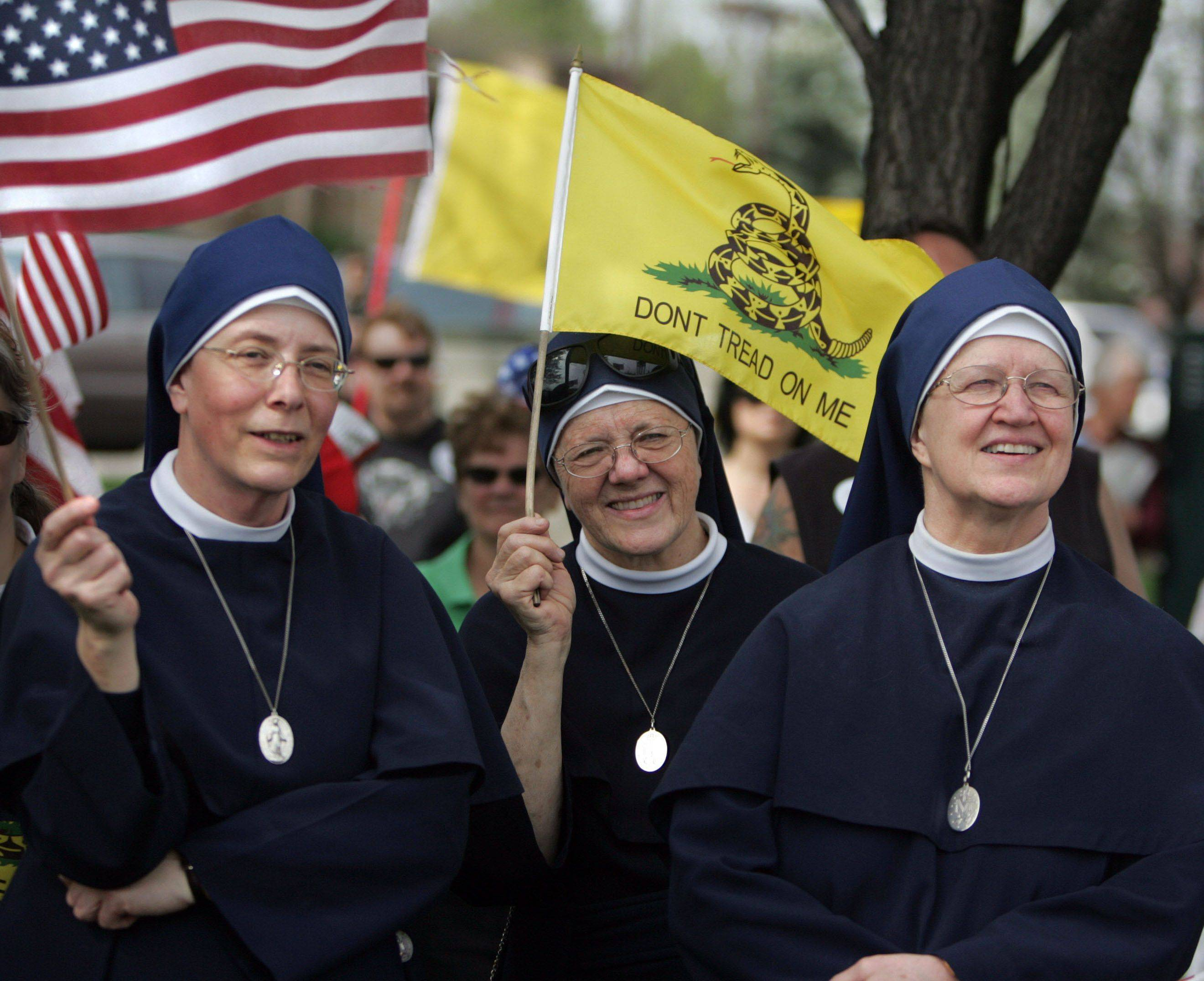 Sister Rose Bernadette, left to right, sister John Marie, and Mother Mary Patrick cheer on speakers at the Tea Party's Taxed Enough Already rally at Volunteer Plaza.