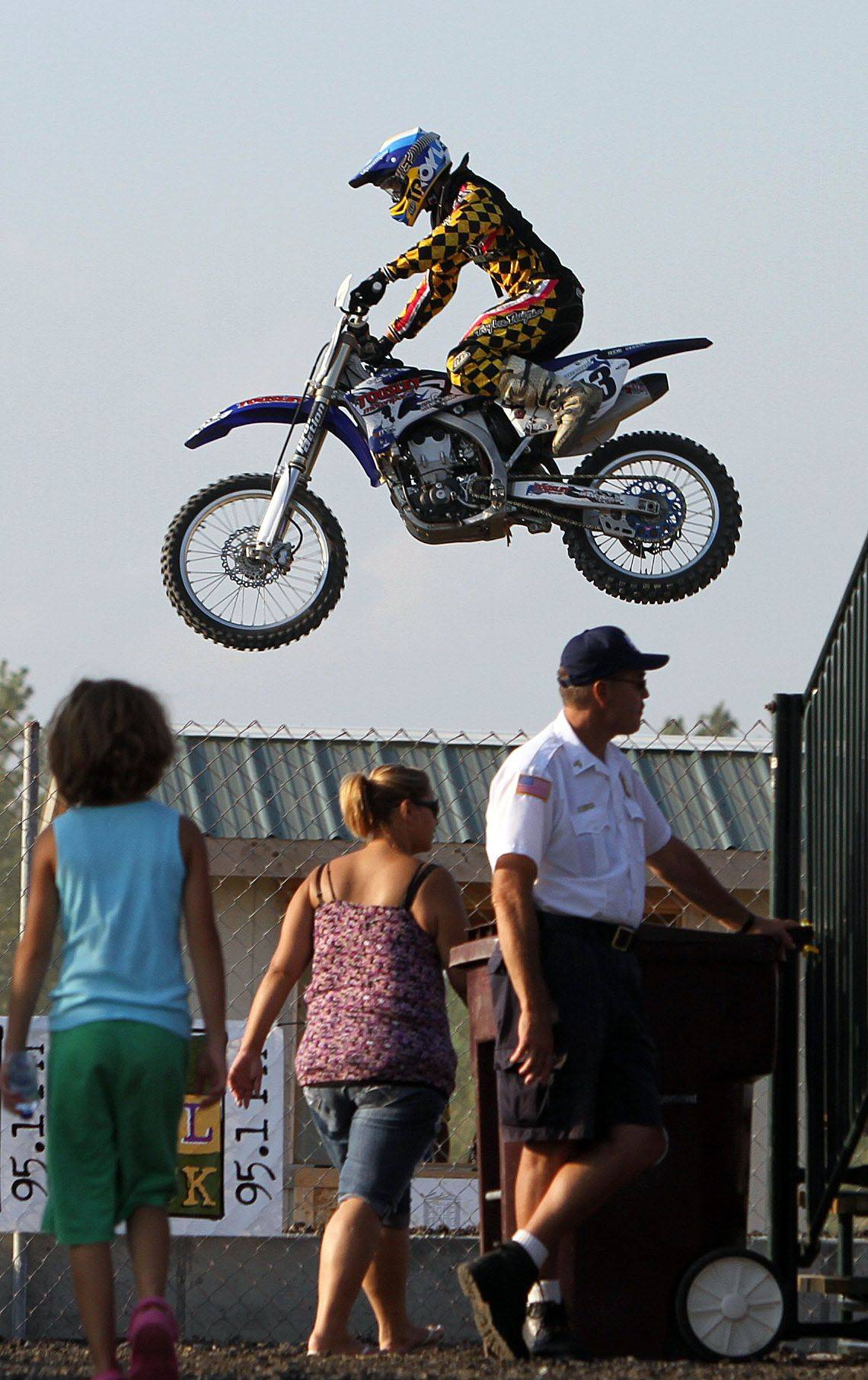 Motocross riders appear to be flying over spectators heads during their practice Tuesday evening at the Lake County Fair in Grayslake.