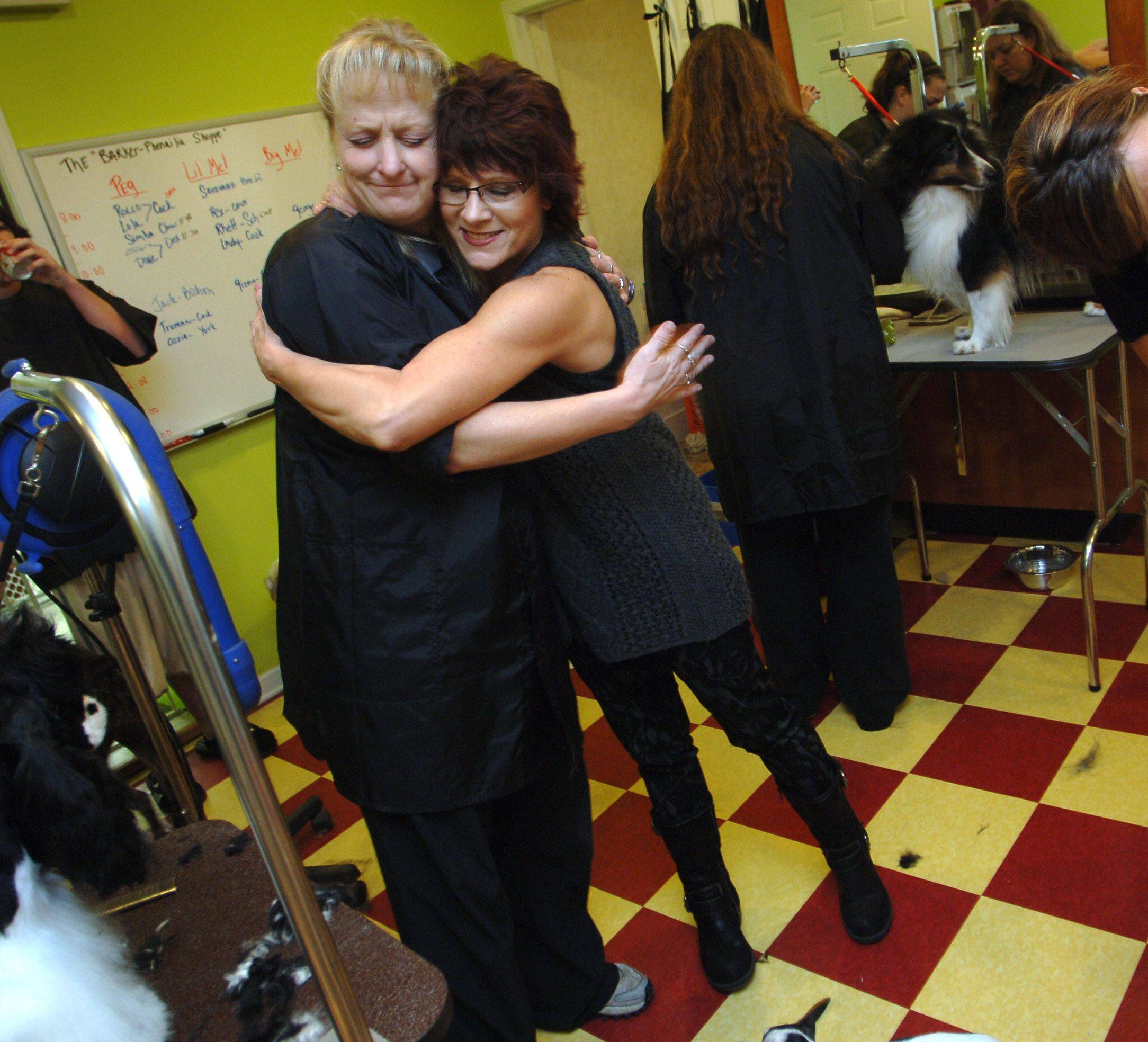 Peg Sennett, left, has relocated and opened her Barker Shoppe Dog Grooming Salon after fire damaged the downtown Antioch business last week. The shop is set up in the rear of Hairaphernailia whose owner, Kathi Thompson, gives Peg a hug Monday.