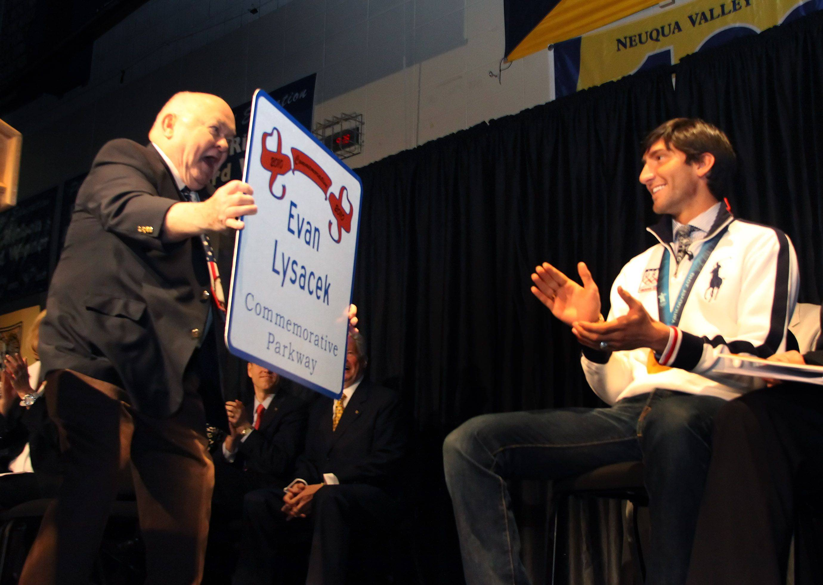 Mayor George Pradel shows Evan Lysacek a sign that will be up at the school as Lysacek returns to Neuqua Valley High School as part of Evan Lysacek Day in Naperville on Friday.