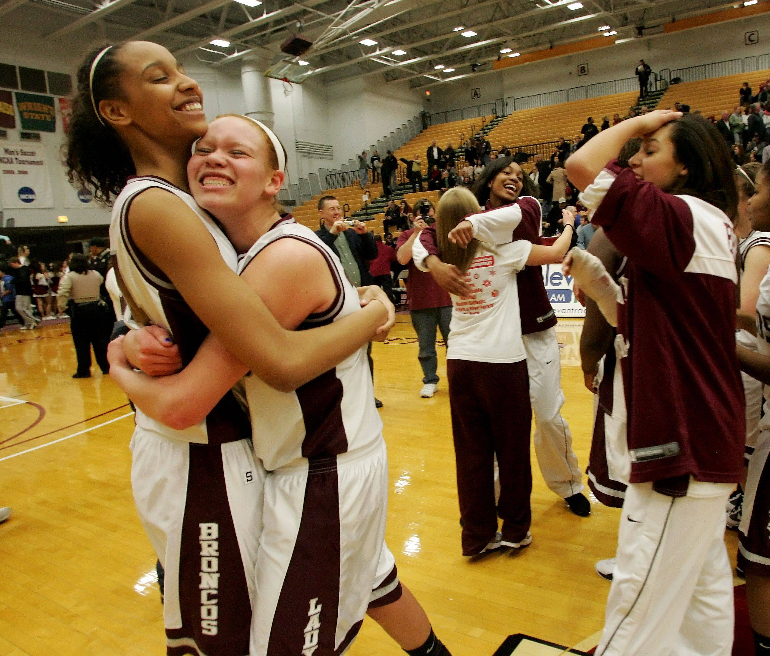 Diamond Thompson, left gives a hug to Whitney Adams, both of Montini after they beat Trinity in Class 3A supersectional girls basketball Monday at Loyola University in Chicago.