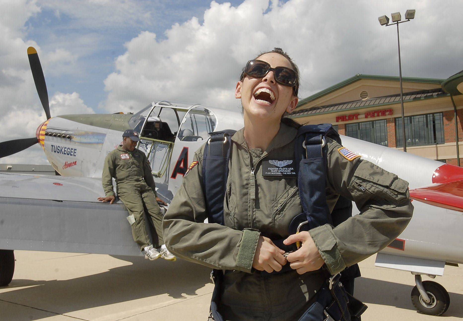 Suzy Sparacio of Naperville grins from ear to ear after her half-hour flight at Schaumburg Airport in a P51-C Mustang flown by Brad Lang, background, son of a Tuskegee Airman. Her flight was a 26th birthday present given to her by family friend David Mullins of Darien.