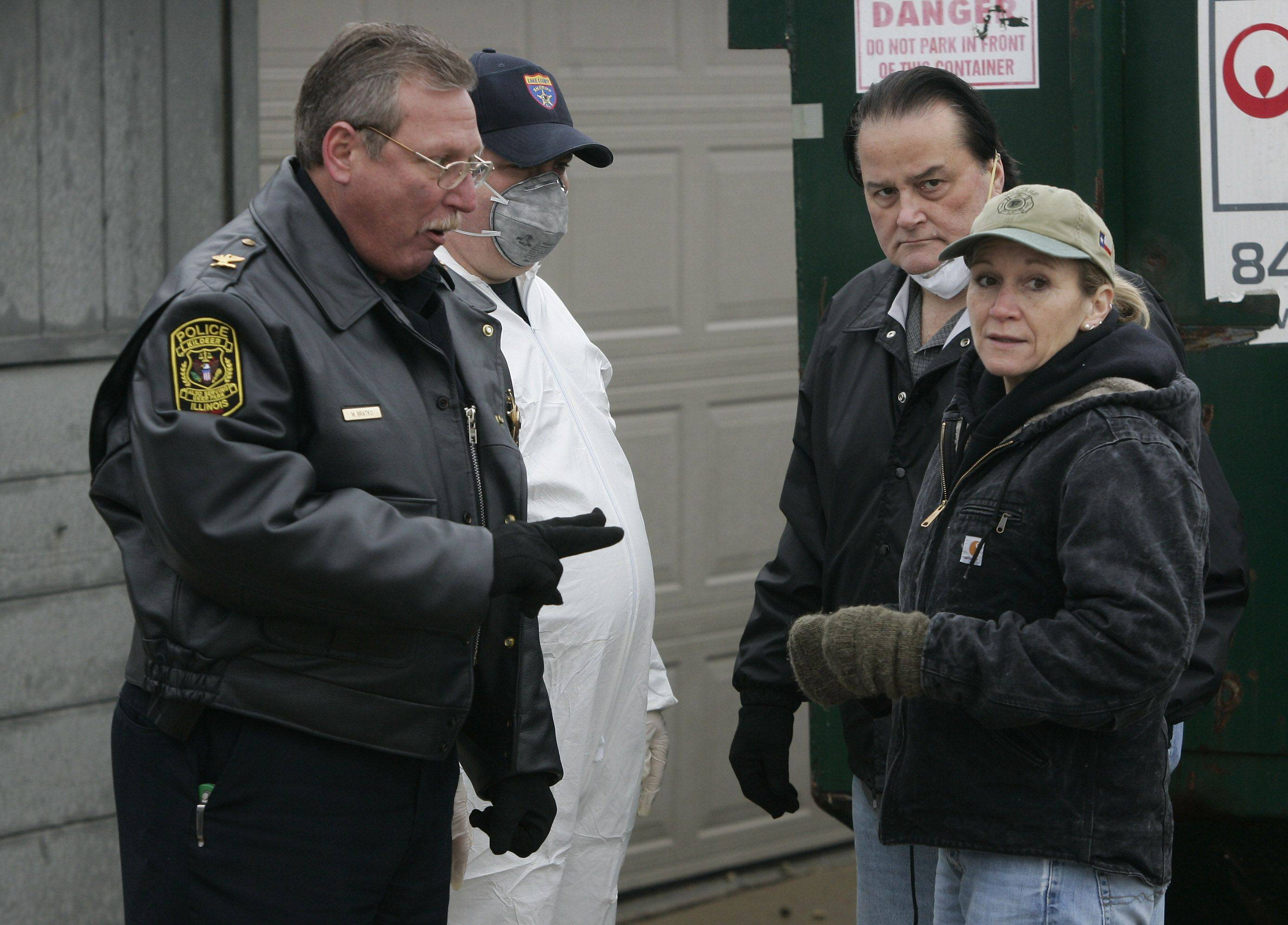 Kildeer police Cmdr. Mike Bratko, left, and Lake County sheriff's investigators talk to animal rescue specialist Dana Deutsch, right, as they investigate the scene at Muddy Paws Dog Rescue in Deer Park.