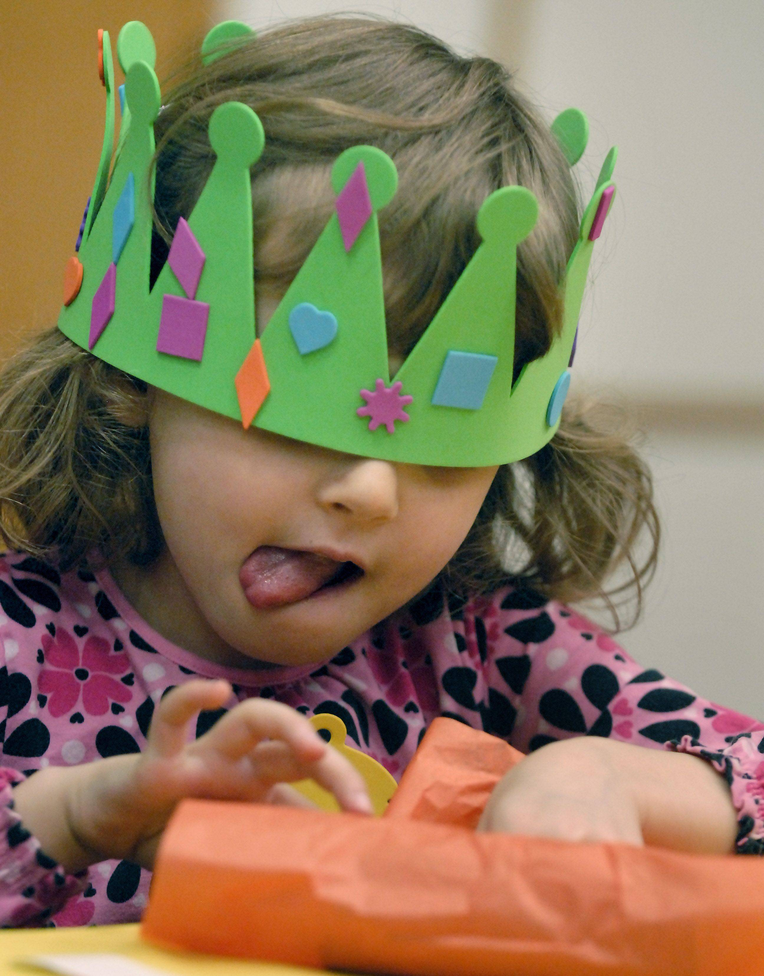 Wearing a king-size crown Rachel Rabe, 4, of Arlington Heights works on her noisemaker during the Almost New Year's party Friday at the Arlington Heights Memorial Library.