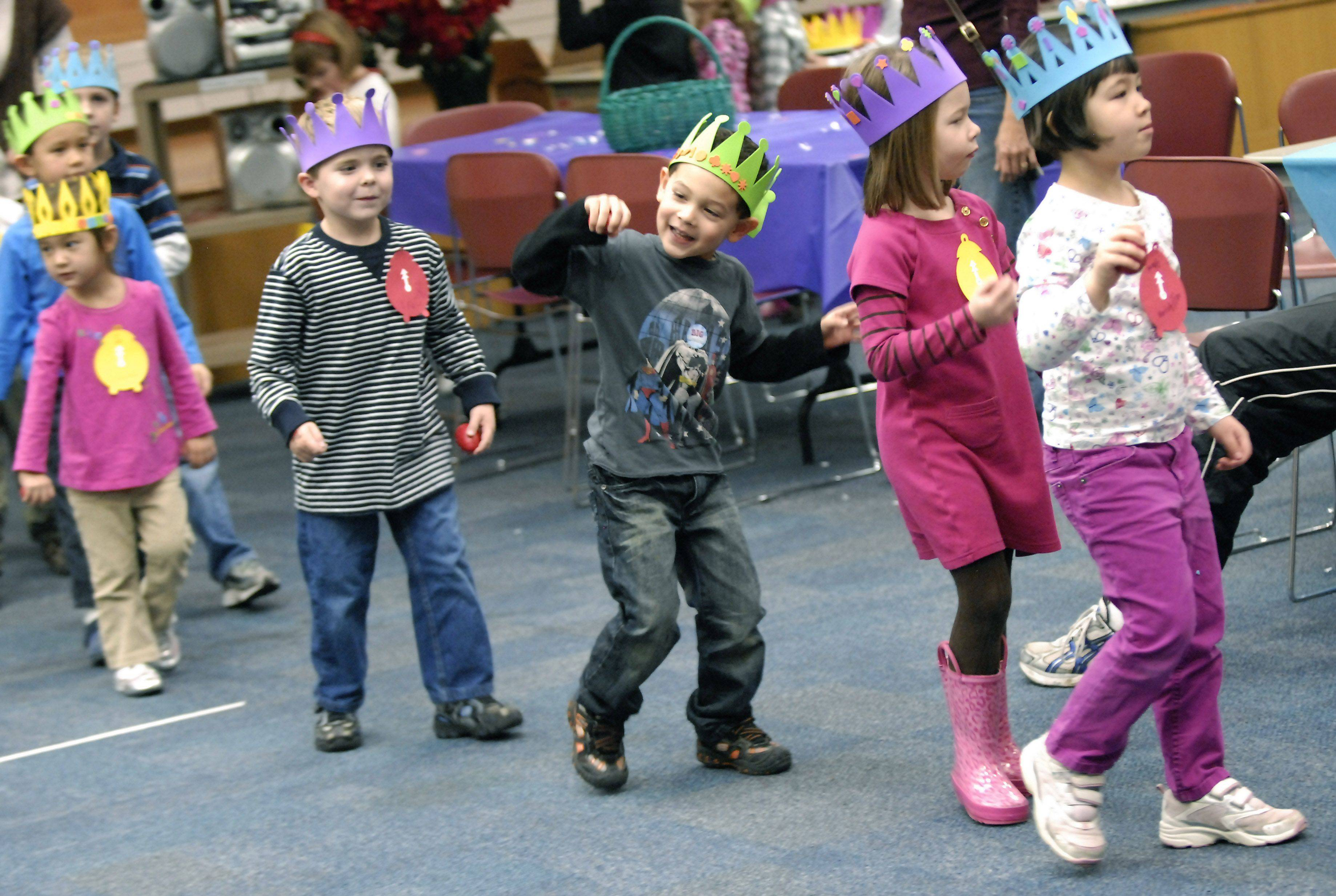 Kids dance in a conga line with Connor Cruz, center, really getting into the spirit of things Friday during the Almost New Year's party at the Arlington Heights Memorial Library.