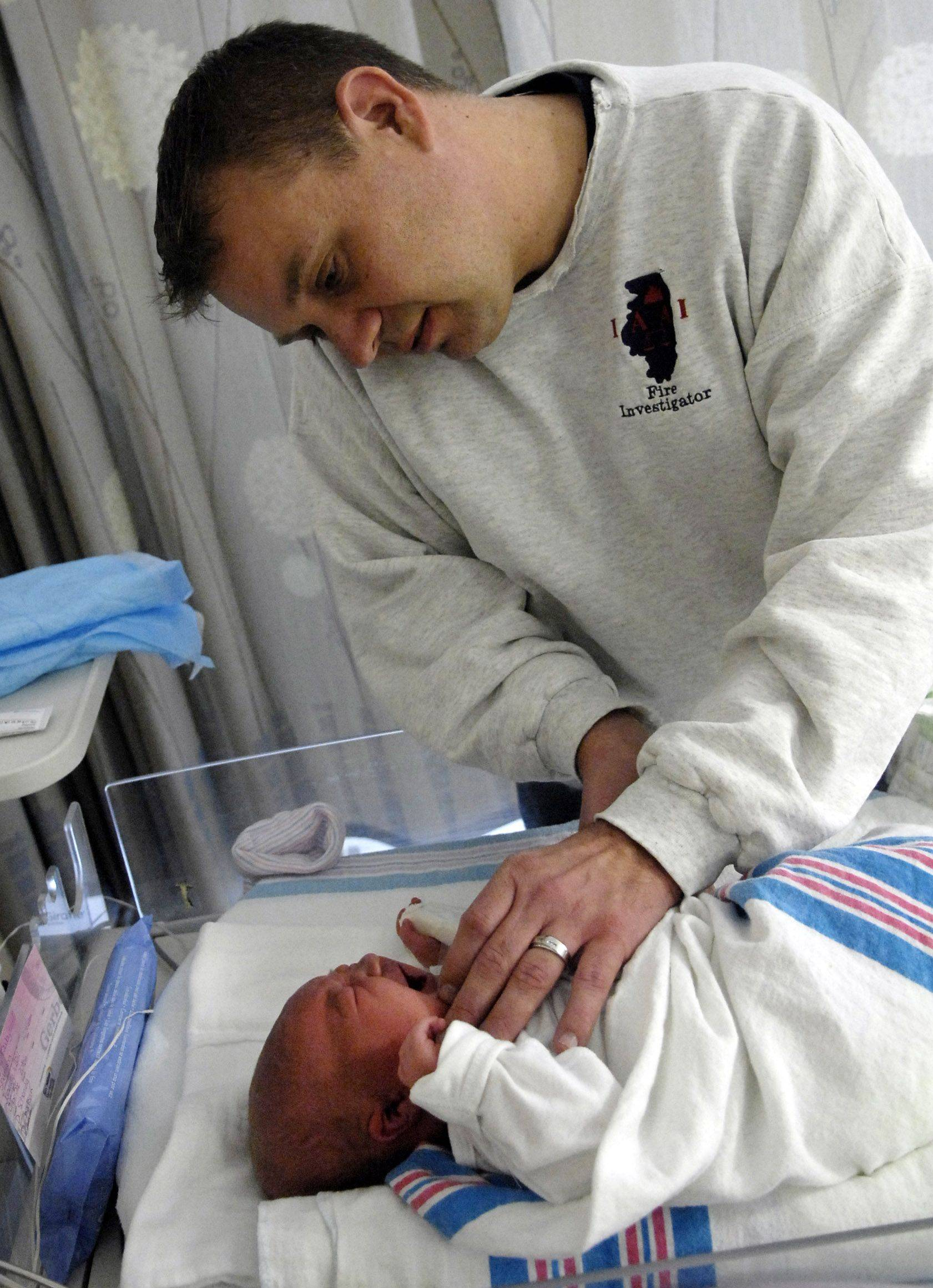 Paul Ross tries to soothe his newborn daughter Caitlin Joya Ross Saturday in the NICU unit at Sherman Hospital in Elgin. Caitlin was the first baby born in Kane County in 2011, emerging at 12:45 a.m. and weighing in at 9 pounds 3 ounces for Paul and mom Shannon.