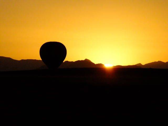 A hot air balloon ride magically rises from the sand at dawn in Namibia in the Sand Dune Sea.
