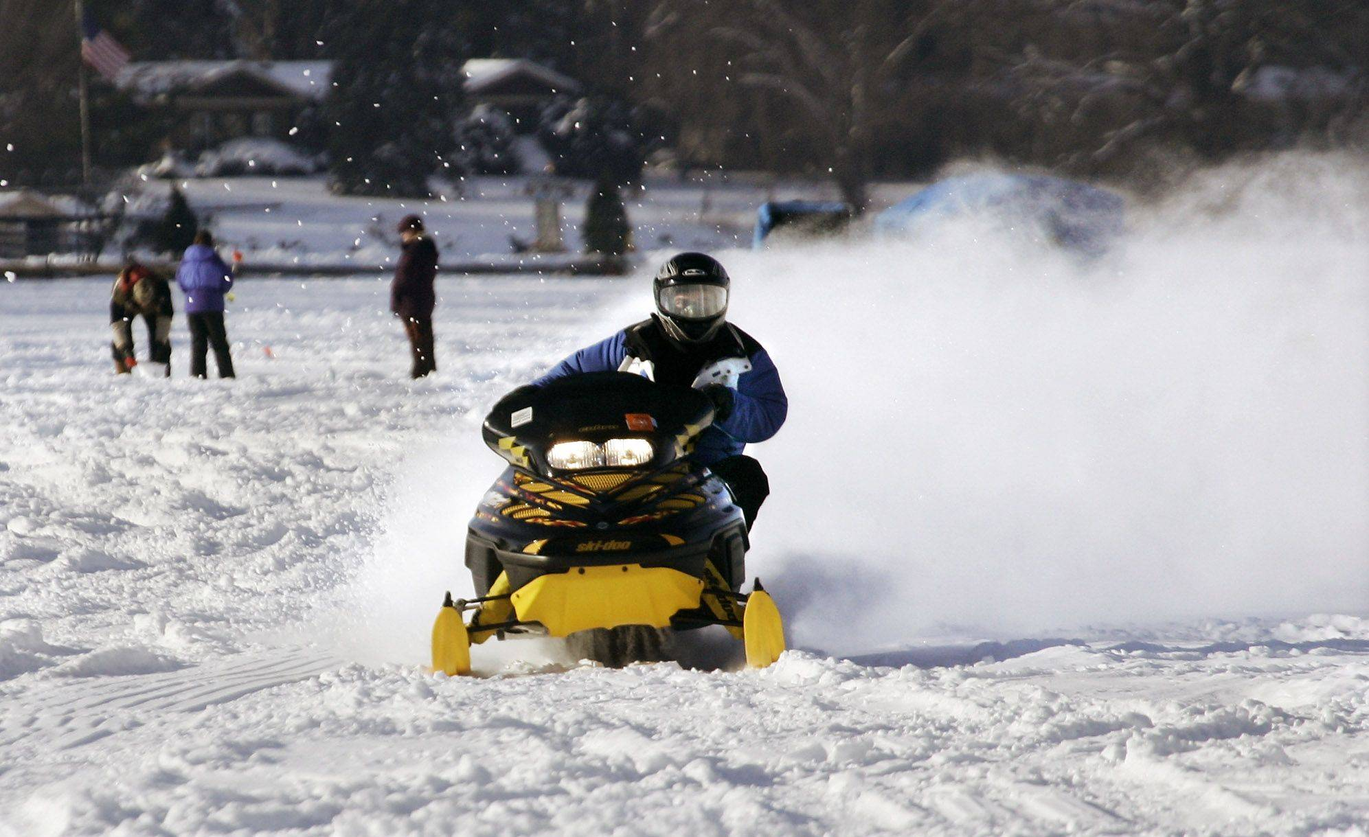 Joe Scavelli of Lake Zurich takes advantage of the beautiful weather to ride his snowmobile Monday on Gages Lake.