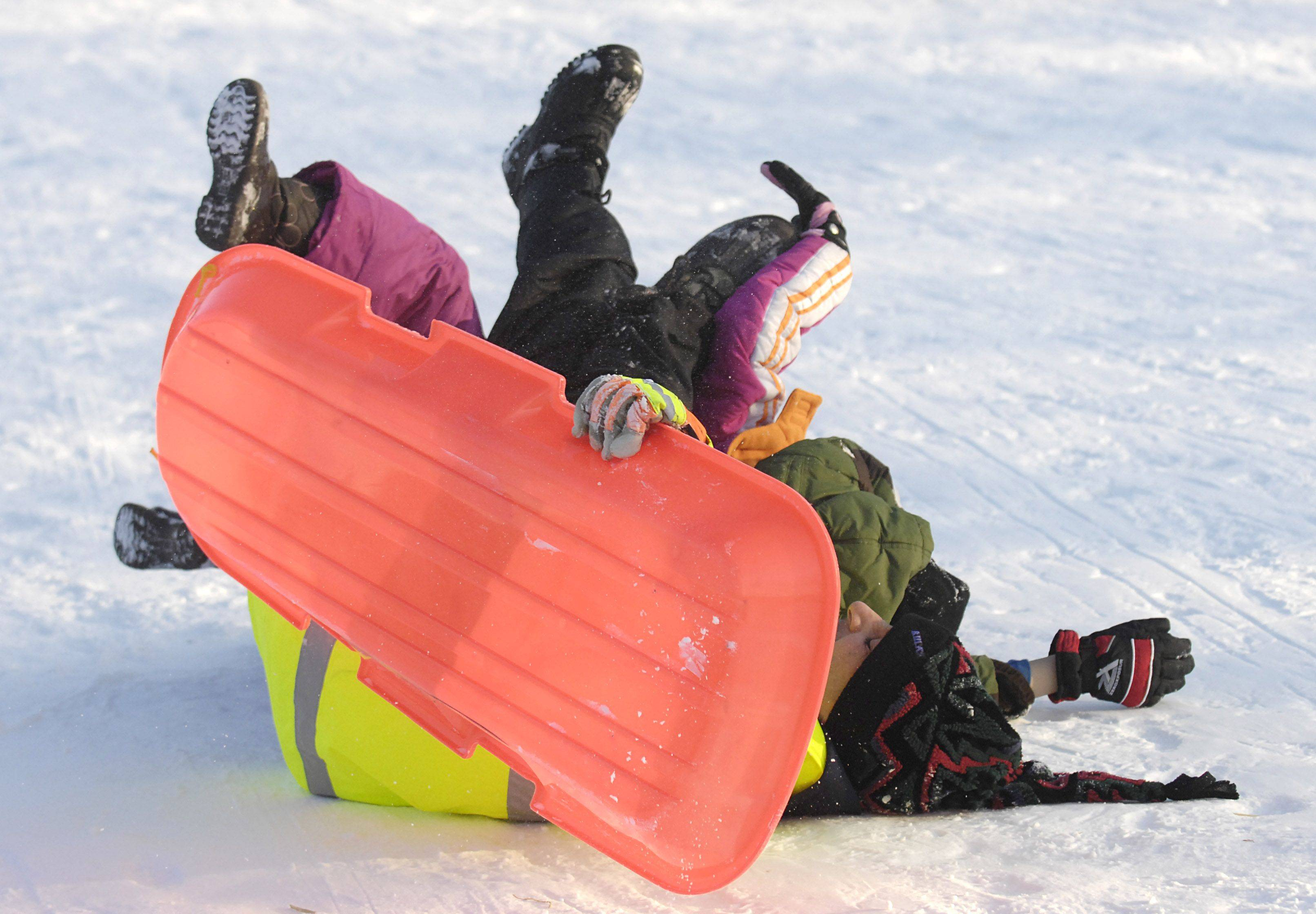 It's a tangle of legs in the air as Dave Giandinoto and his children, Dominic, 11, and Mia, 9, tumble to a stop at the bottom of the hill at Fabyan Forest Preserve in Geneva on Tuesday, December 28. The trio were smoothly sailing down the hill until the sled took a turn and dumped them out.