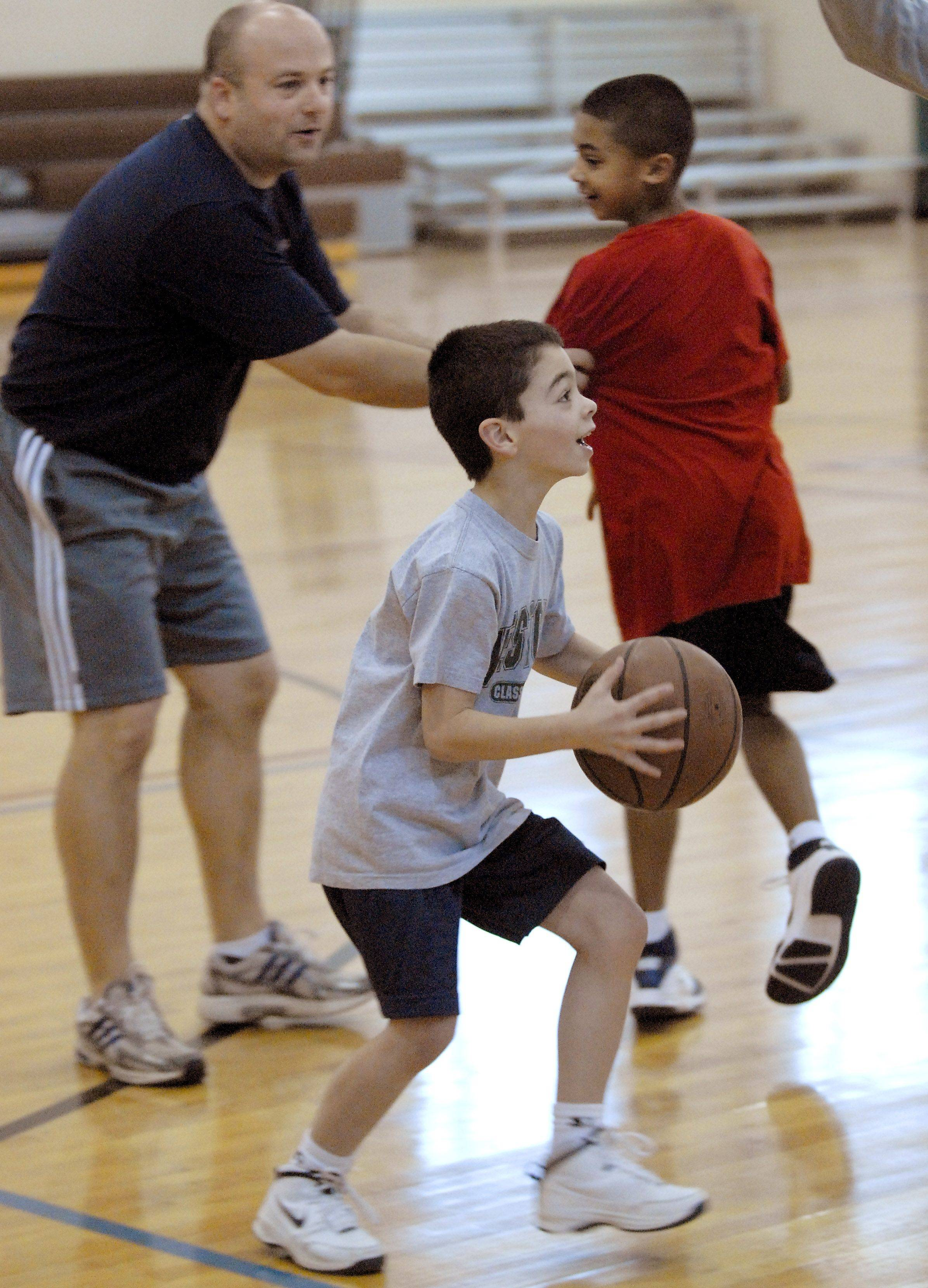 Luke Duffer, 7, gets past his dad Pete Duffer with help from Max Christie, 7, while playing basketball during open gym at Pioneer Park Tuesday in Arlington Heights. All three are from Arlington Heights.