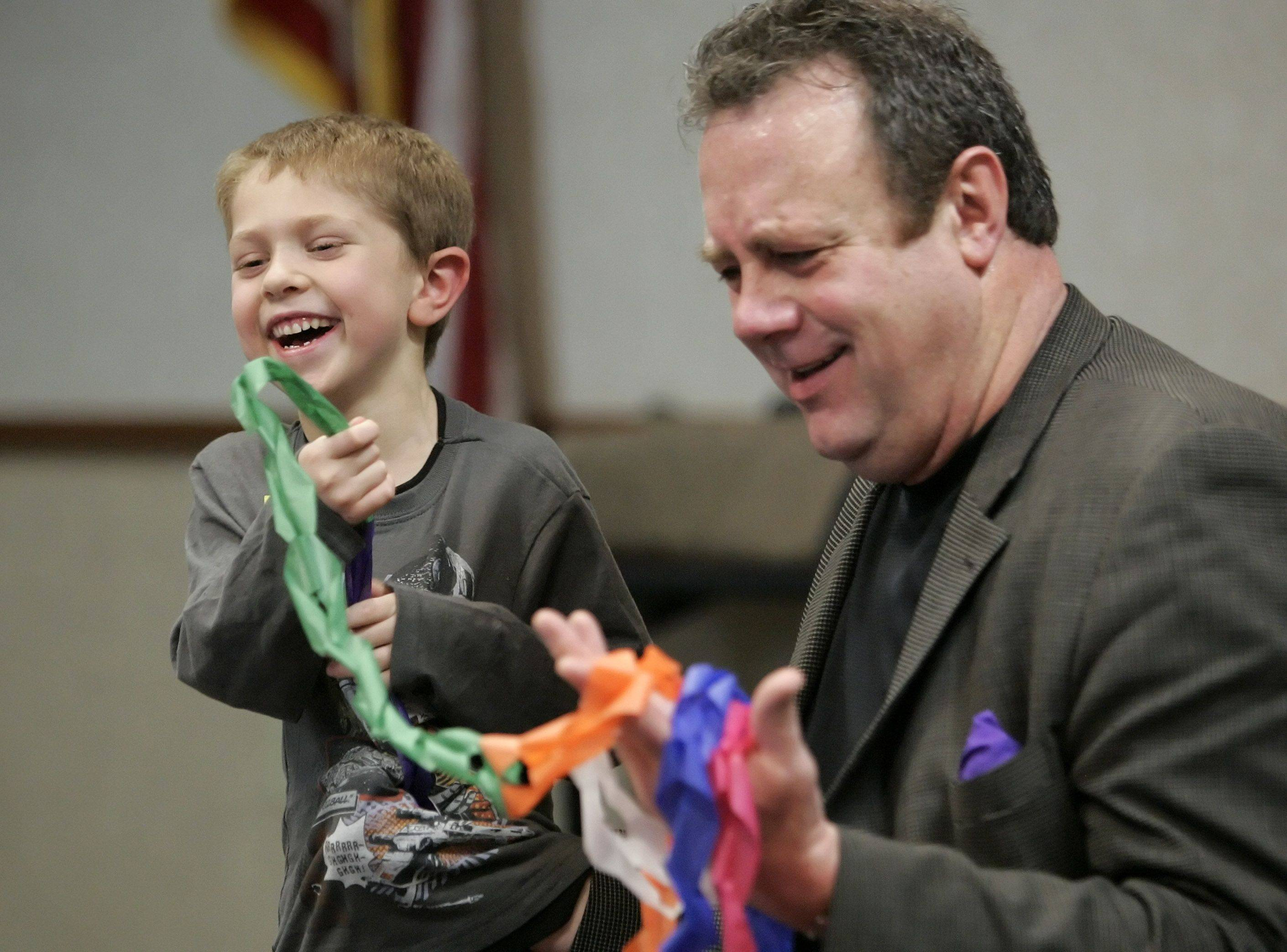 Magician Dennis DeBondt of Chicago gets some help from seven-year-old Paden Roma of Gurnee during a show at Fremont Public Library in Mundelein Thursday.