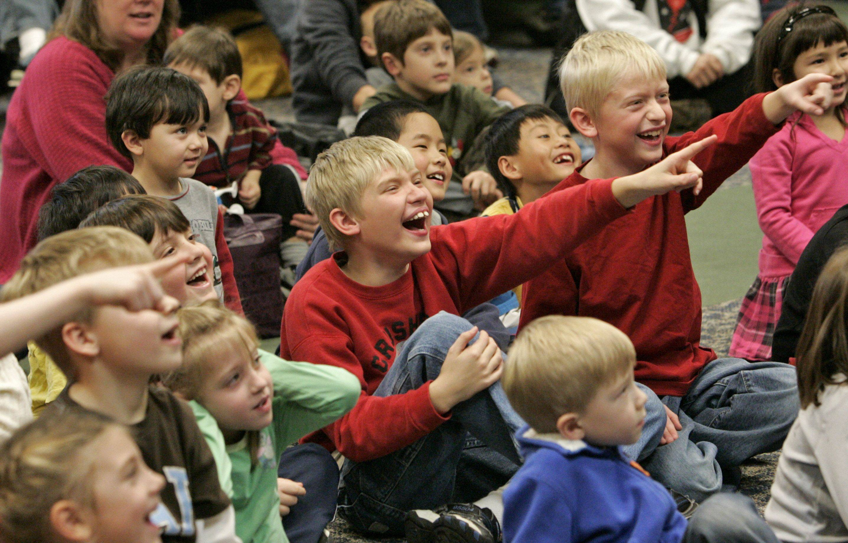 Kids react during a show by magician Dennis DeBondt of Chicago at Fremont Public Library in Mundelein Thursday.