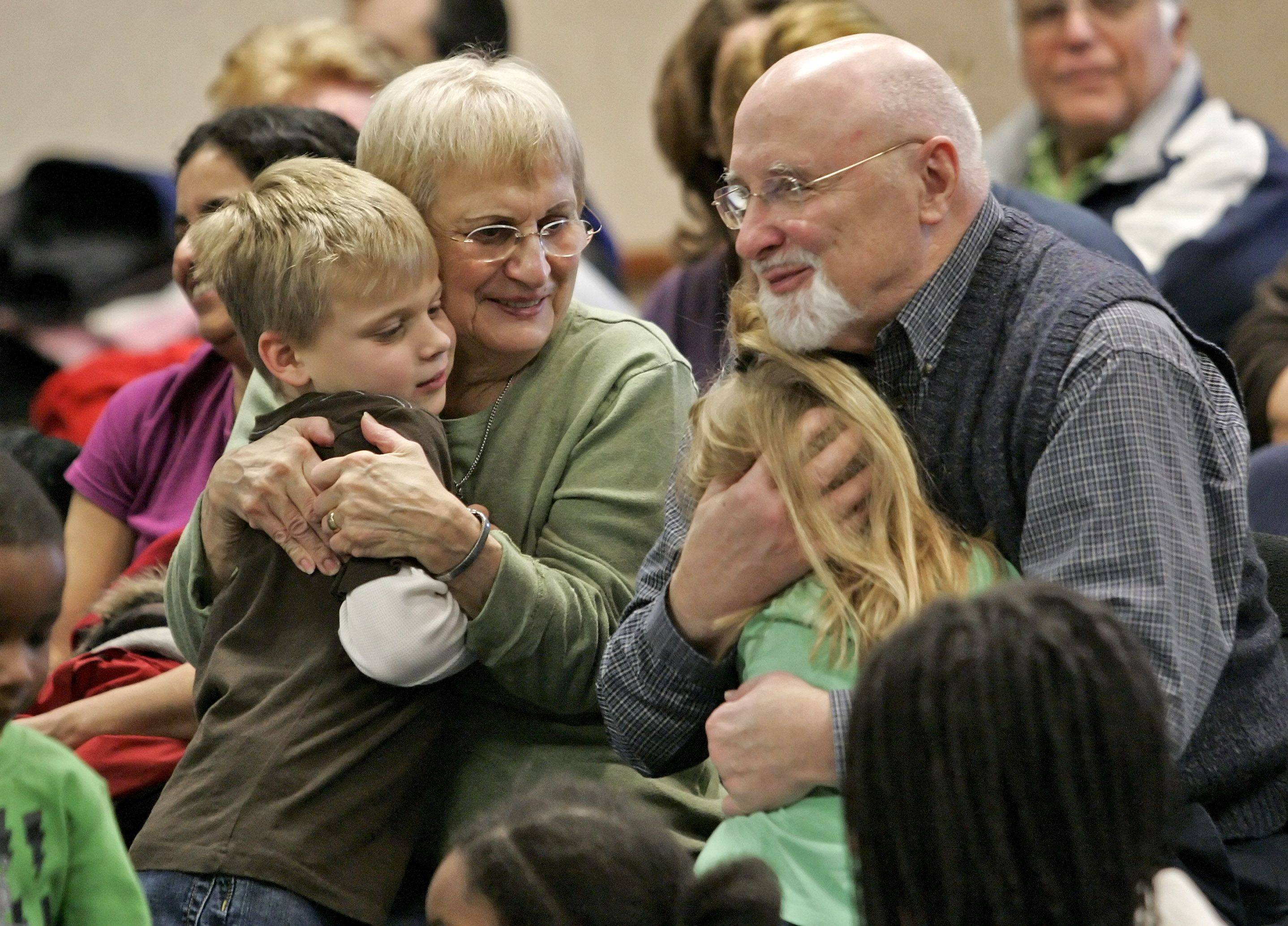Tillie and John Scanlan get a hug from their grandkids Henry Scanlan, 7 and Shannon Doyle, 5 after a countdown to noon New Year's at Fremont Public Library in Mundelein Thursday. All are from Mundelein.