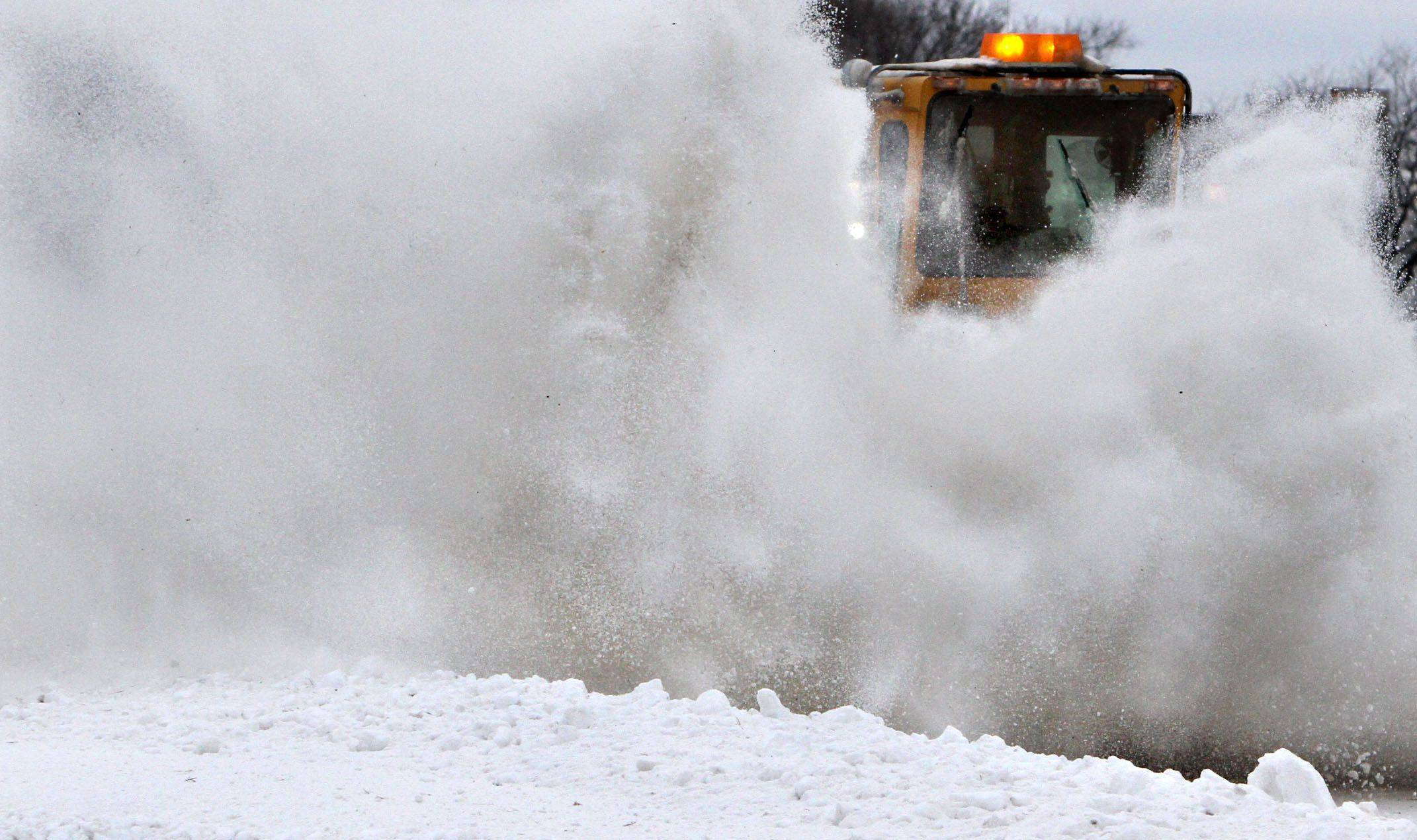A large snowplow removes snow from a runway at Chicago Executive Airport in Wheeling on Sunday, December 26.