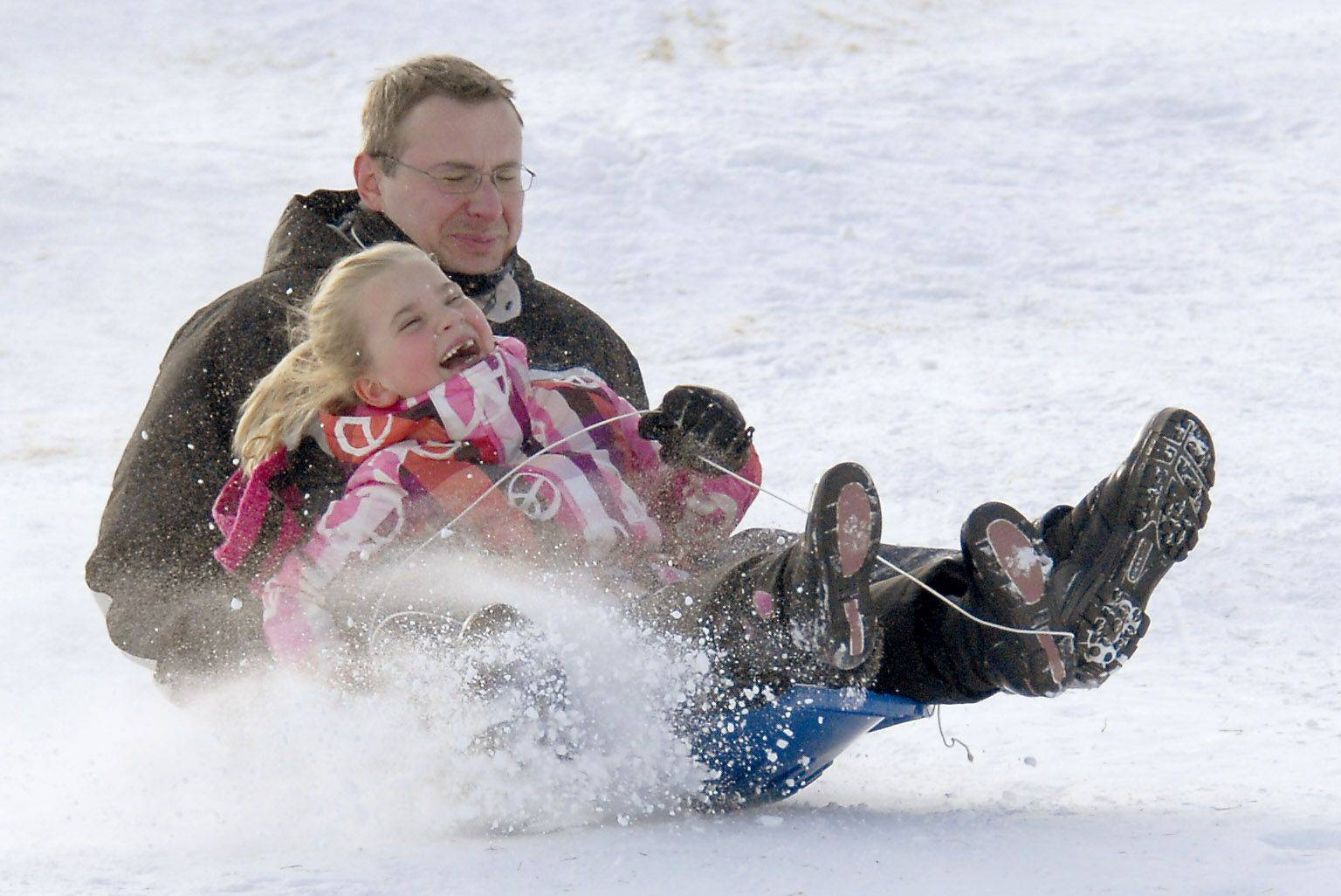 Emil Chwojnicki and his daughter Victoria, 7, kick up some powder on the sled hill Monday afternoon in Sunset Park in Arlington Heights.