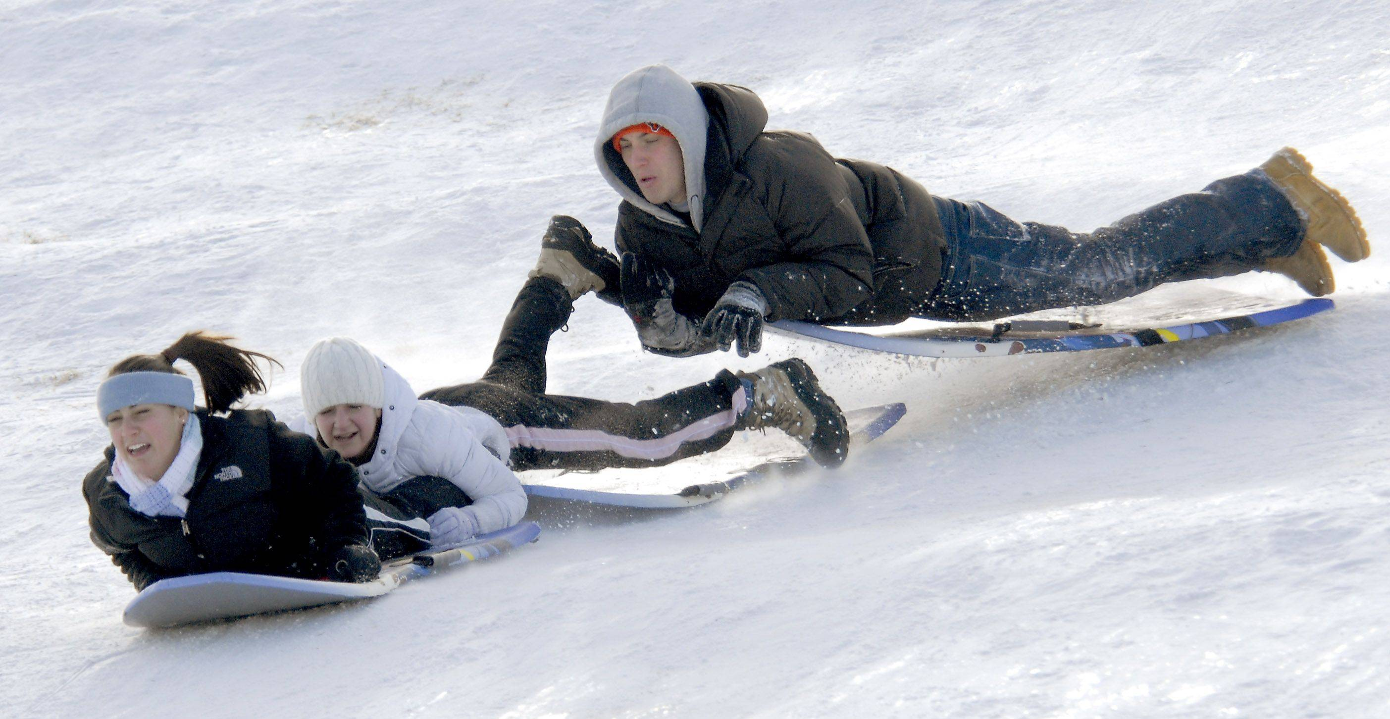 Janelle Schneider, from left, Jenna Schneider and Branden Ladewig, all of Rolling Meadows, catch some air on the moguls at the sled hill in Sunset Park Monday afternoon.