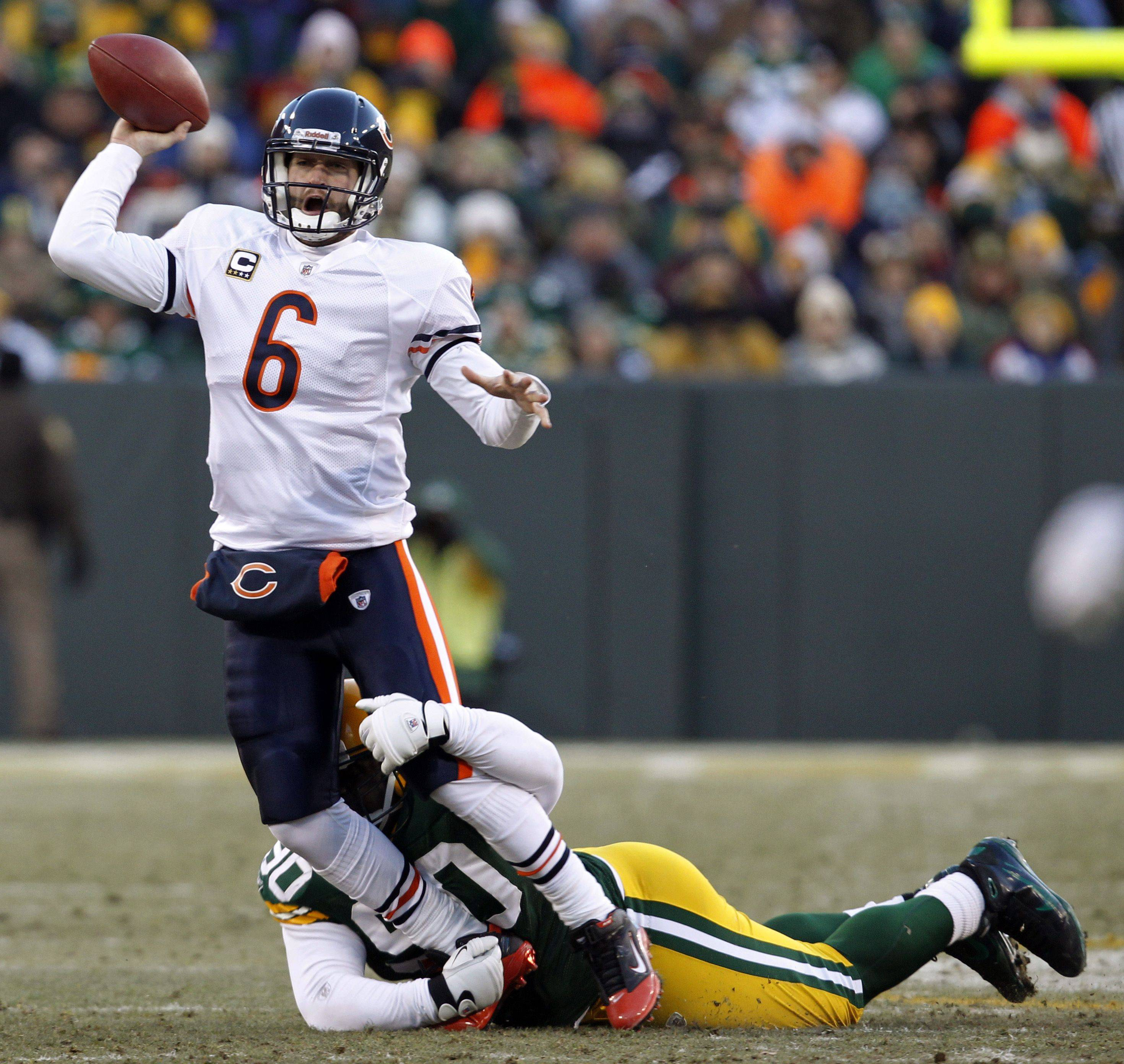 Chicago Bears' Jay Cutler throws with Green Bay Packers' B.J. Raji grasping his legs during the first half.