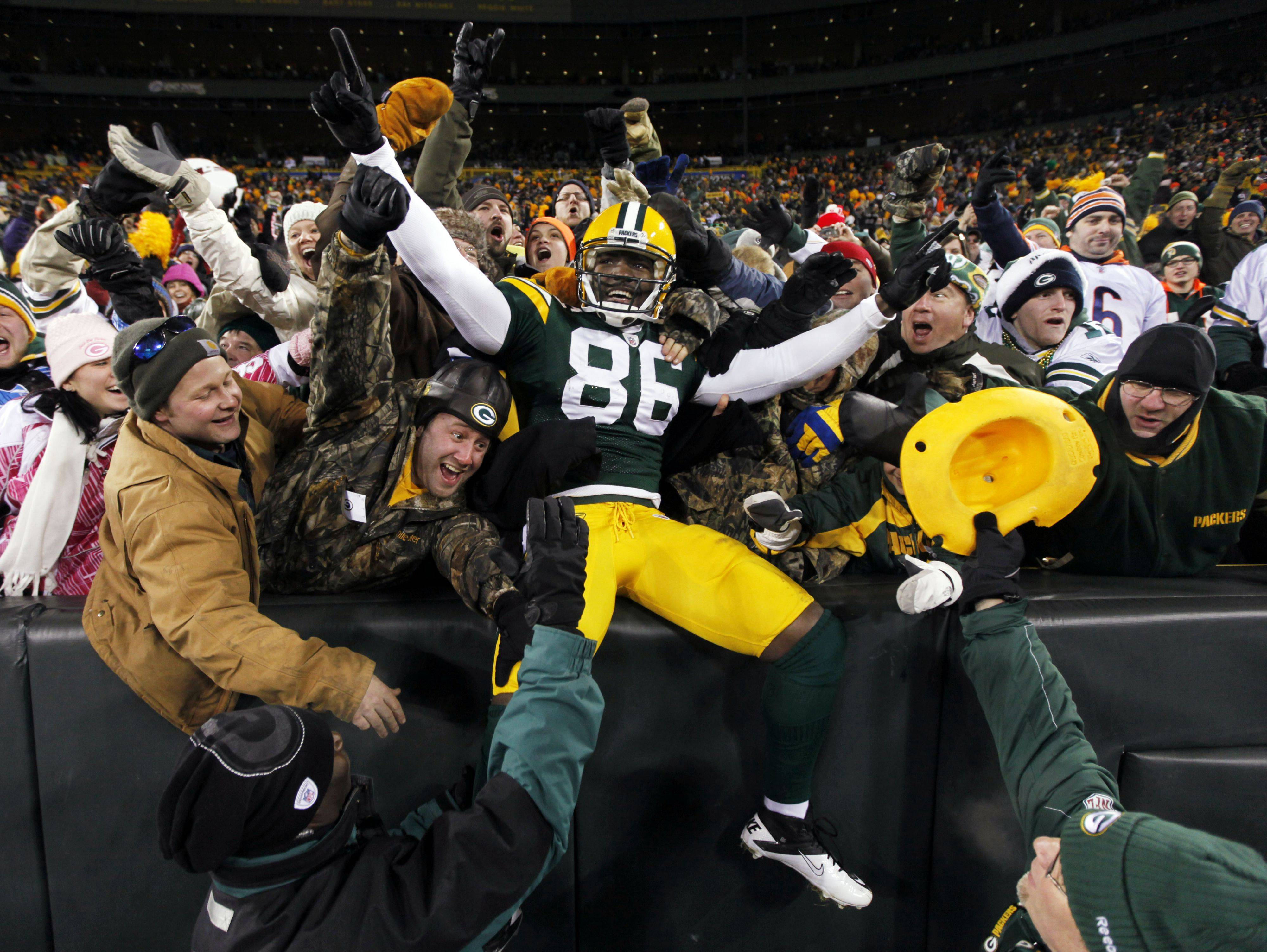 Green Bay Packers' Donald Lee celebrates with fans after catching a touchdown pass during the second half.