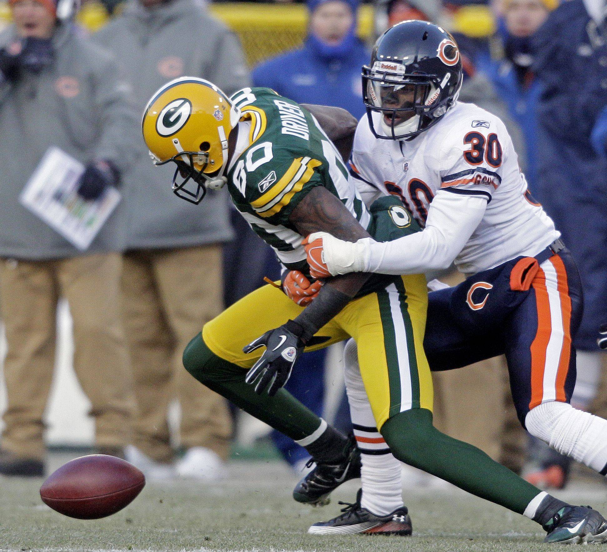 Green Bay Packers' Donald Driver fumbles as he is tackled by Chicago Bears' D.J. Moore after a catch during the first half. Driver recovered the fumble.