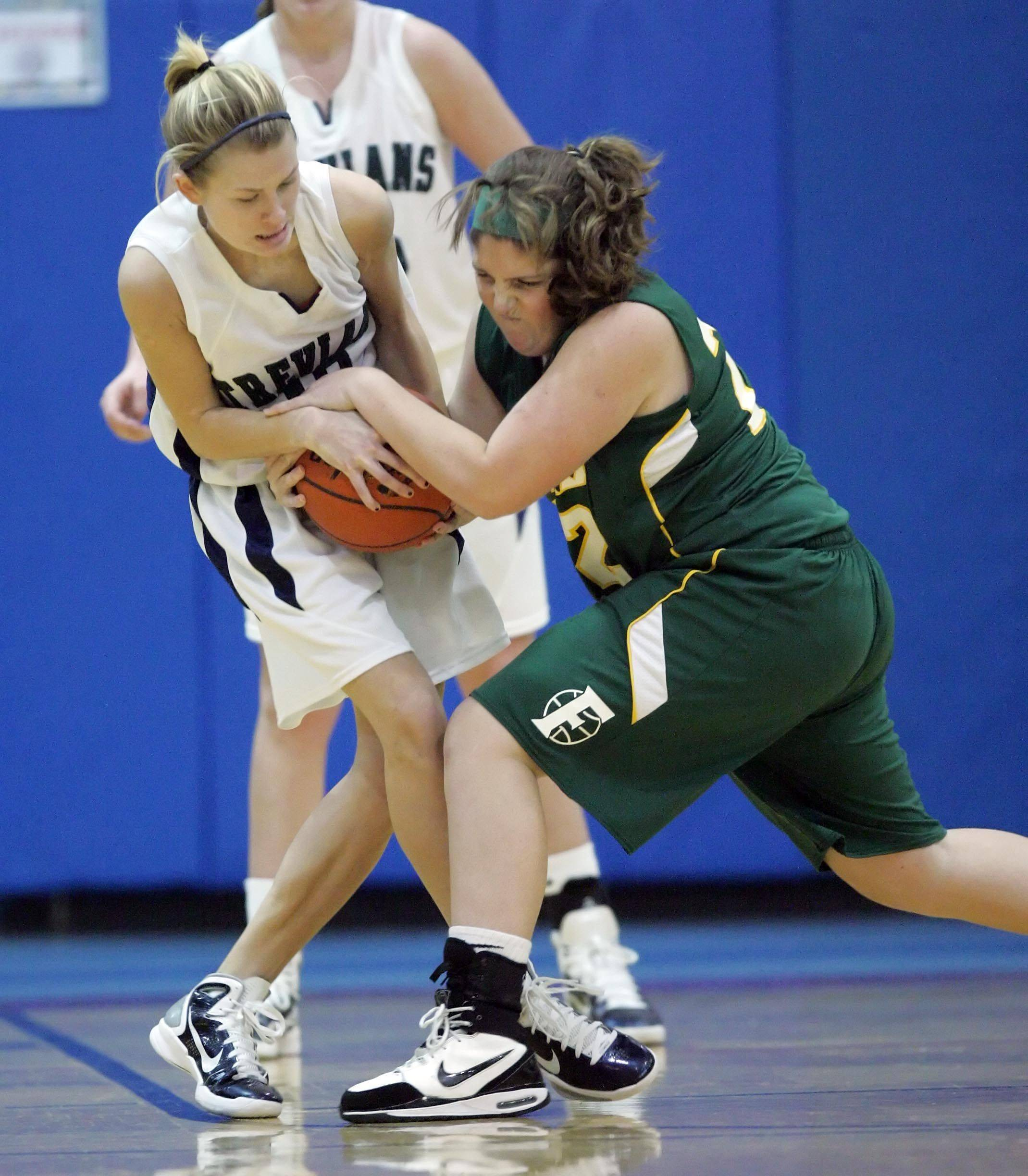New Trier's Meg Rosinski, 10, wrestles Fremd's Megan Horn, 22, during their Charger Classic girls basketball game in Carpentersville Thursday.