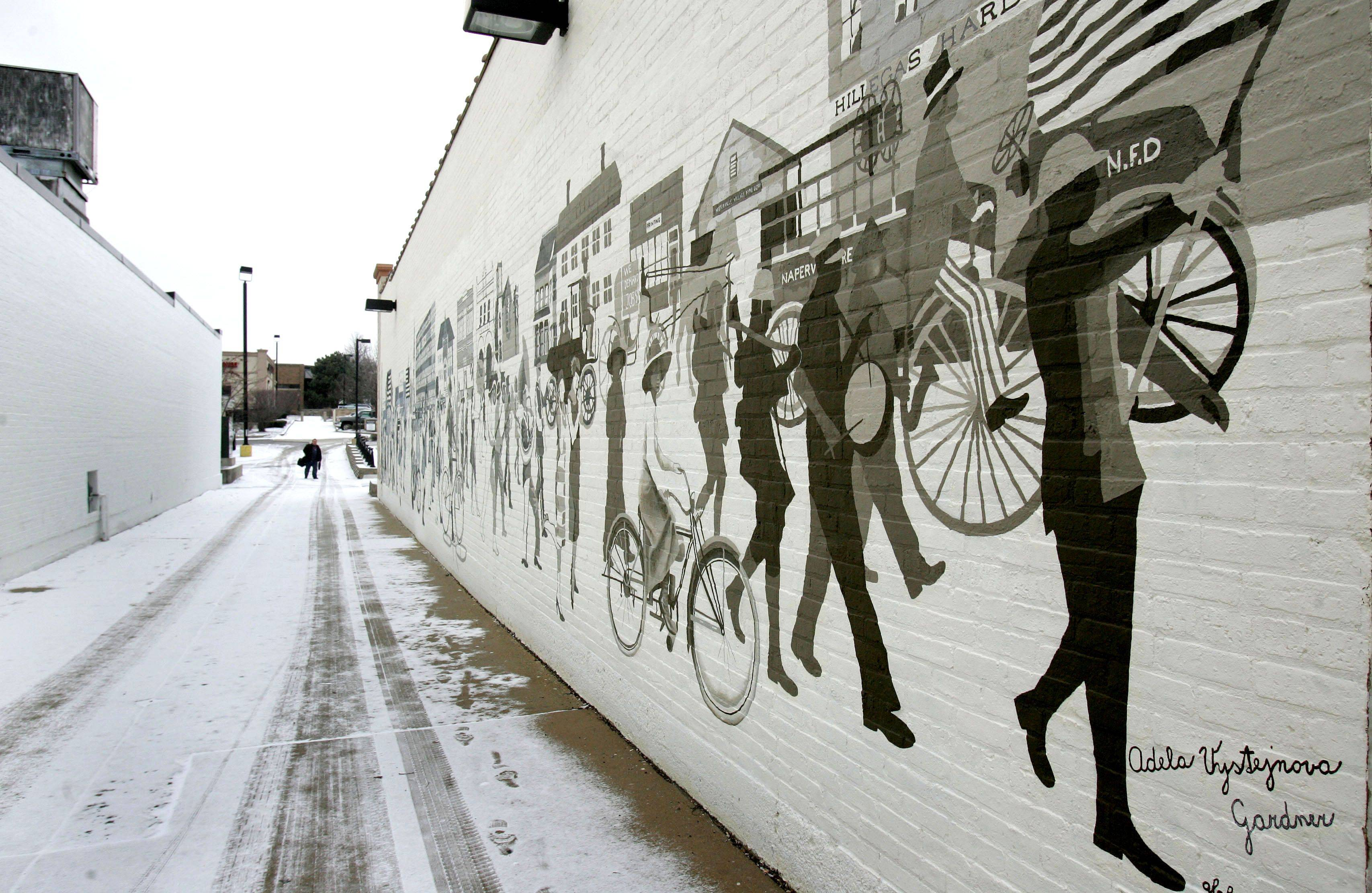 "Artist Adela Vystejnova Gartner has completed the first phase of her ""Parade of the Century"" mural in downtown Naperville. She will begin painting the second section on Monday."