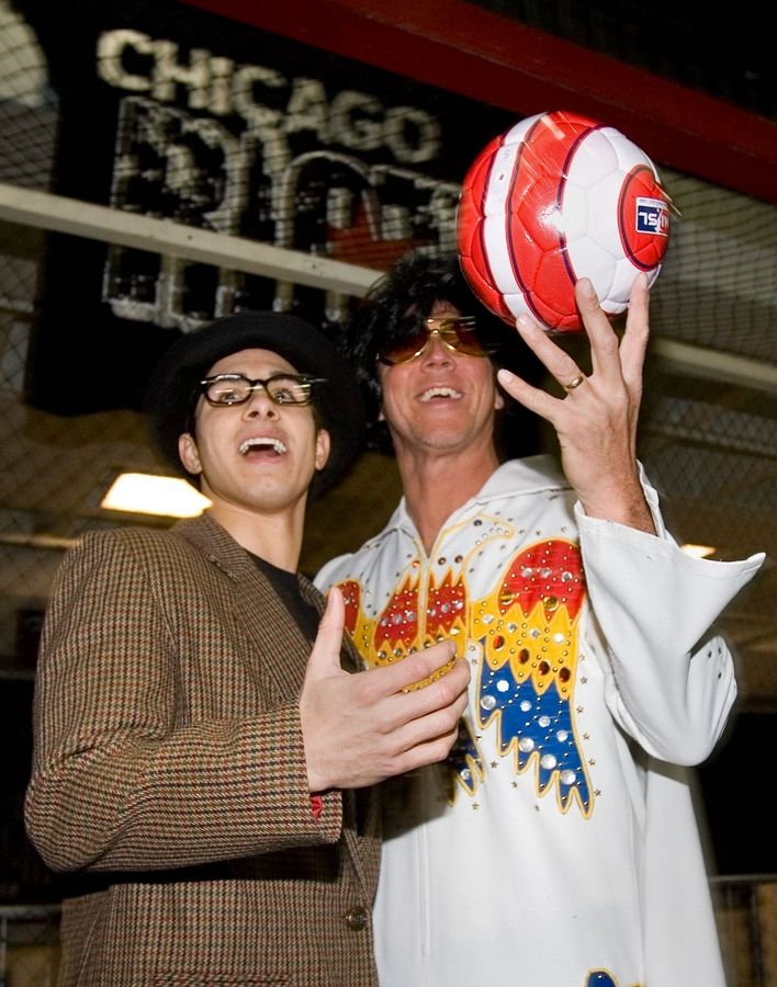 "Jeff Kraft, coach of the Chicago Riot, a new indoor soccer team, previews the ""Elvis Night"" attire for Sunday night's game at the Odeum in Villa Park. At left is midfielder Marco Sullo, dressed in an Elvis Costello costume. The night will include a quick game between a team of Elvis Presleys and a team of Elvis Costellos."