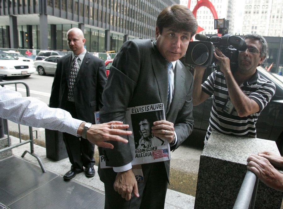 Ex-Gov. Rod Blagojevich, an Elvis fan, holds a sign brought by a supporter comparing him to his idol as his wife Patti tries to pull him into the federal court building in Chicago during his trial last summer.