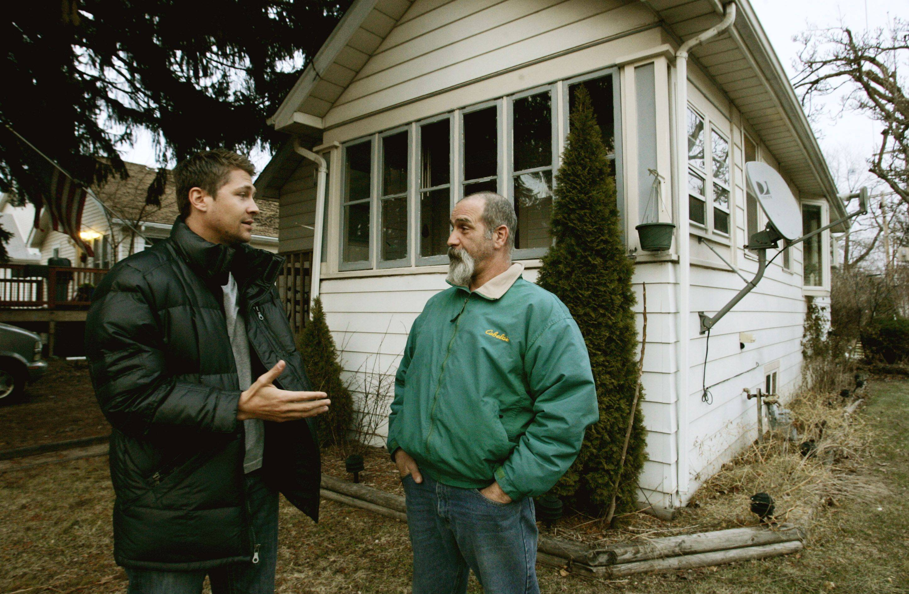 Adam Ackerman, left, a real estate investor who helped start the Foreclosure Defense Group in Rosemont, chats with homeowner David Johnson of Villa Park.