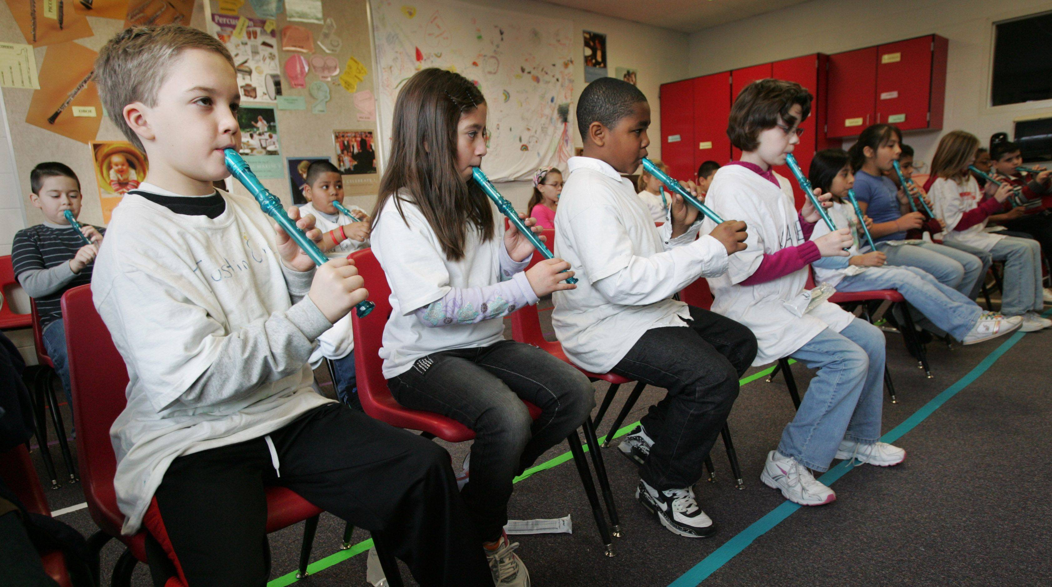 Creekside music students Justin Oine, left, Aimee Jimenez, Christopher Rose and Karen Coombs play some of the first notes on their new recorders Tuesday. The students will be performing with the Elgin Symphony Orchestra in May.