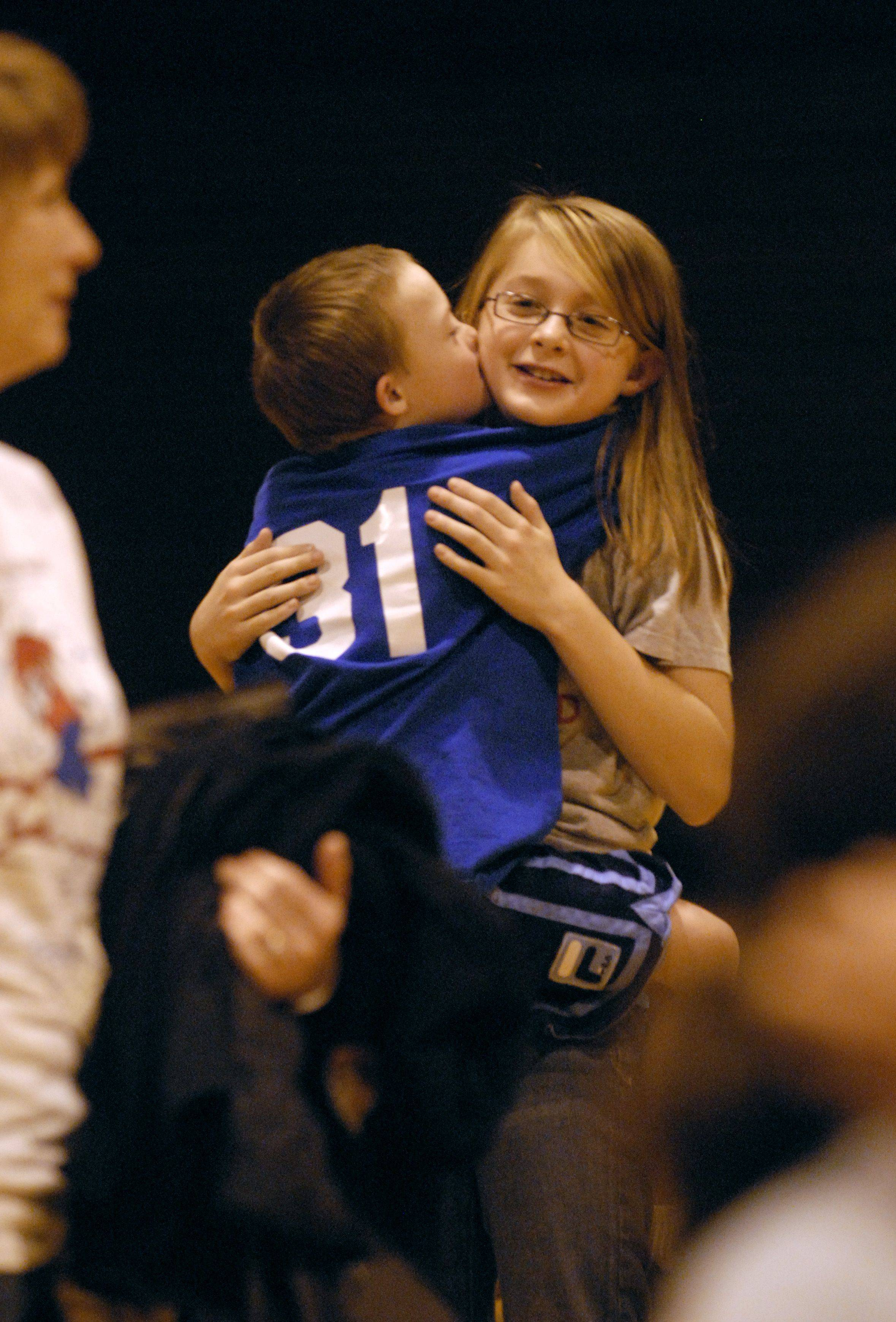 Special Olympics teammates Braden Graves, 9, hugs and kisses his older sister, Kylie Graves, 10, after the ceremony at the Gifford Street Alternative High School gym Thursday night in Elgin.