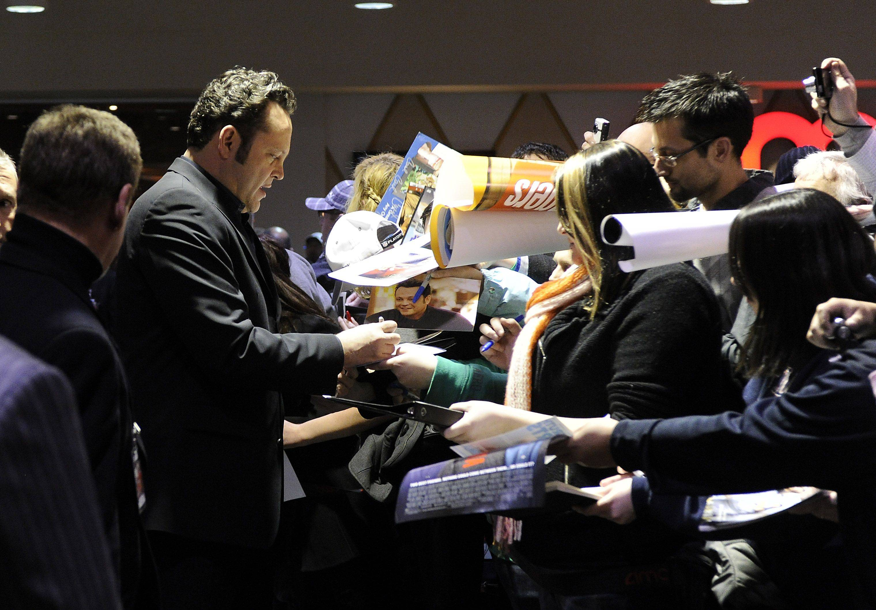 Actor Vince Vaughn signs autographs for fans at the Chicago premiere of the feature film The Dilemma.