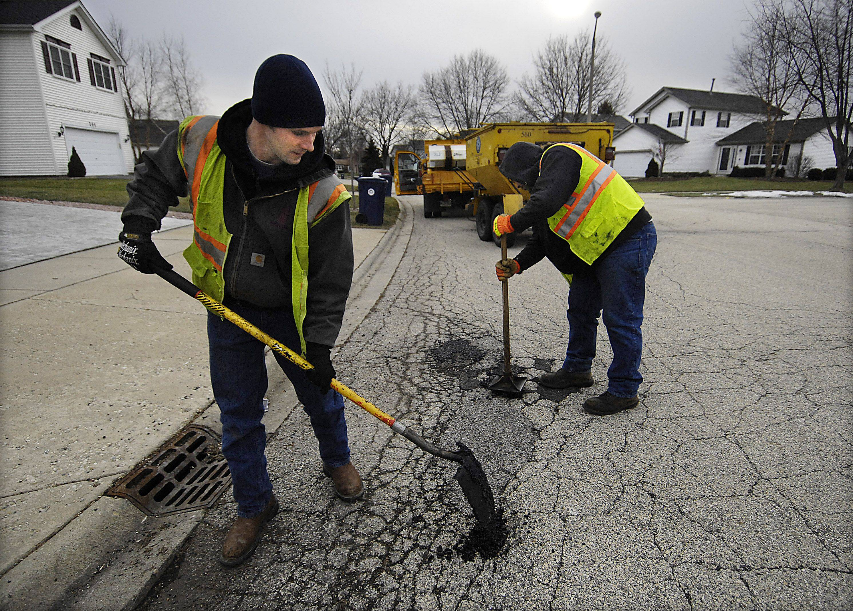 Nick Sheppard shovels asphalt filler as Rick Kempe tamps the mixture tightly into potholes on Glacier Parkway in Algonquin Monday. They fill as many as 100 potholes per day during the winter months.