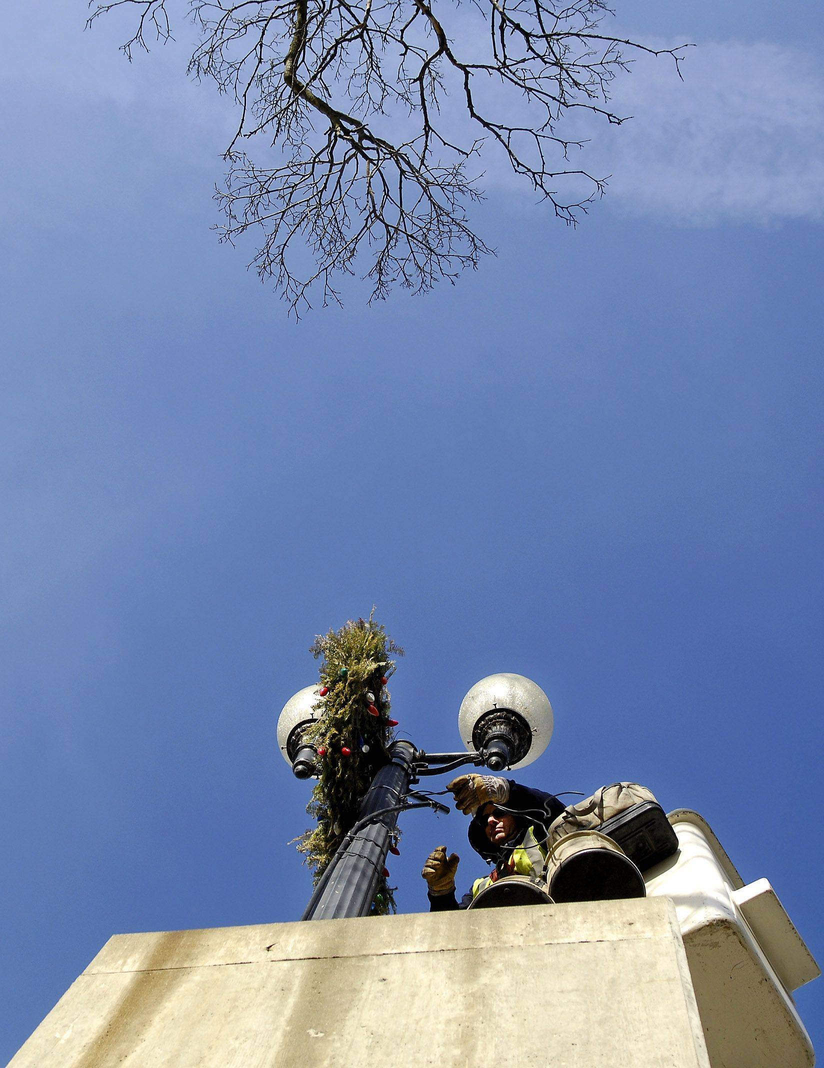 City of Geneva worker Jeff Wilger uses a cherry picker to take down a holiday wreath from a lamp post on the State Street bridge Monday afternoon. Wilger, who said he has worked for the city for 21 years, said it was a few days work to get everything down from downtown out to Kirk Road.