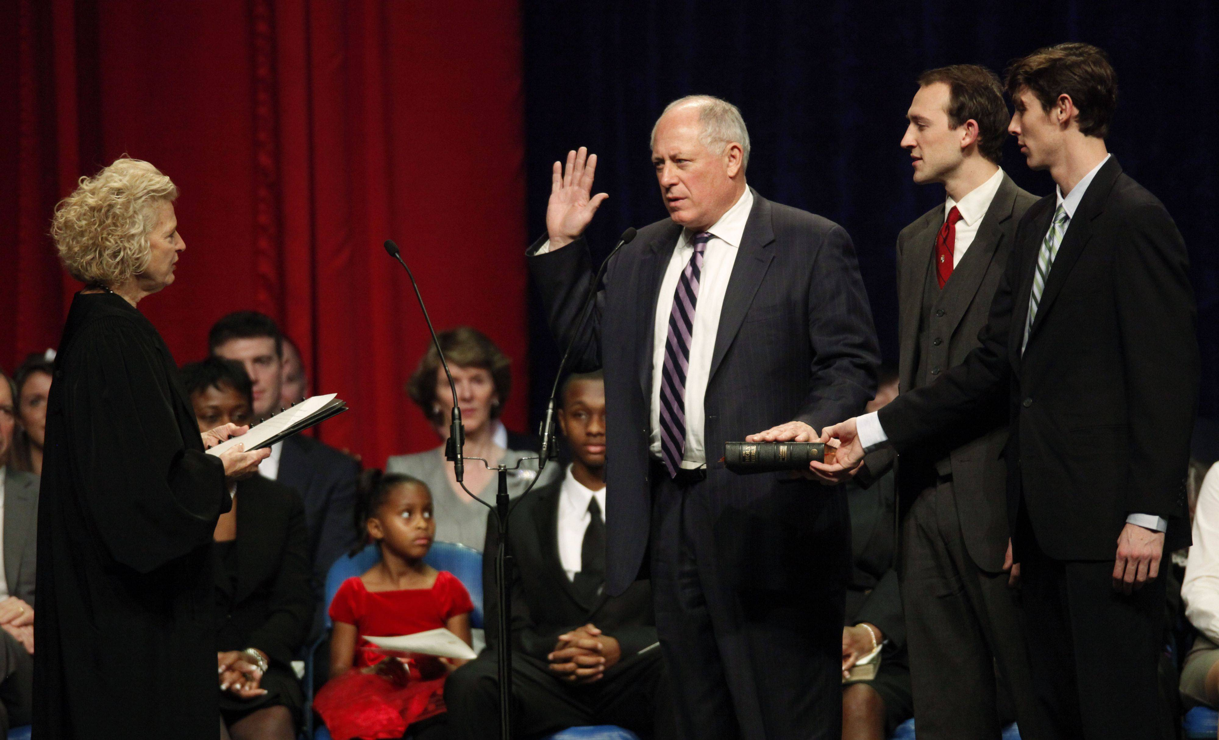 Gov. Pat Quinn, center, takes the oath of office in Springfield from Illinois Supreme Court Justice Anne M. Burke, as Quinn's sons Patrick and David hold the Bible he was sworn in on.