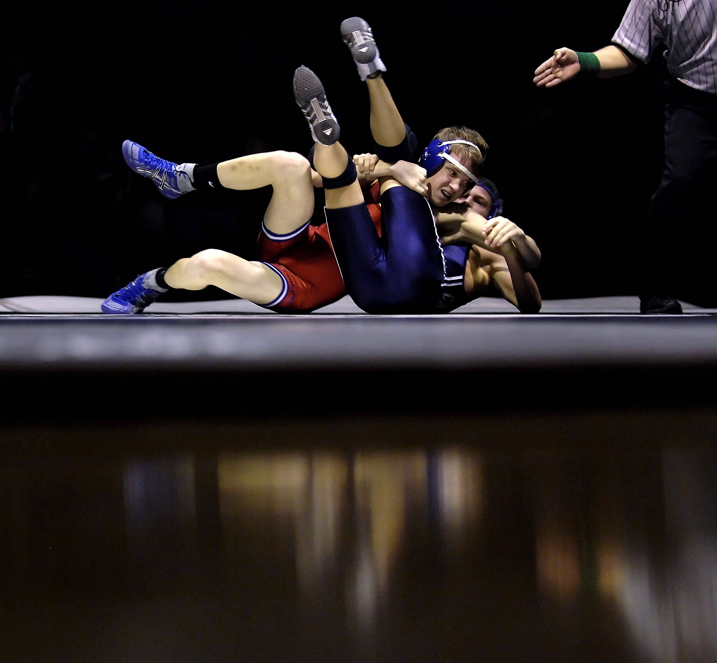 Dundee-Crown's Travell Rounds and Cary-Grove's Zach Spielmann, right, are reflected in the gymnasium floor during their 119-pound match Thursday in Cary. Rounds won the match.