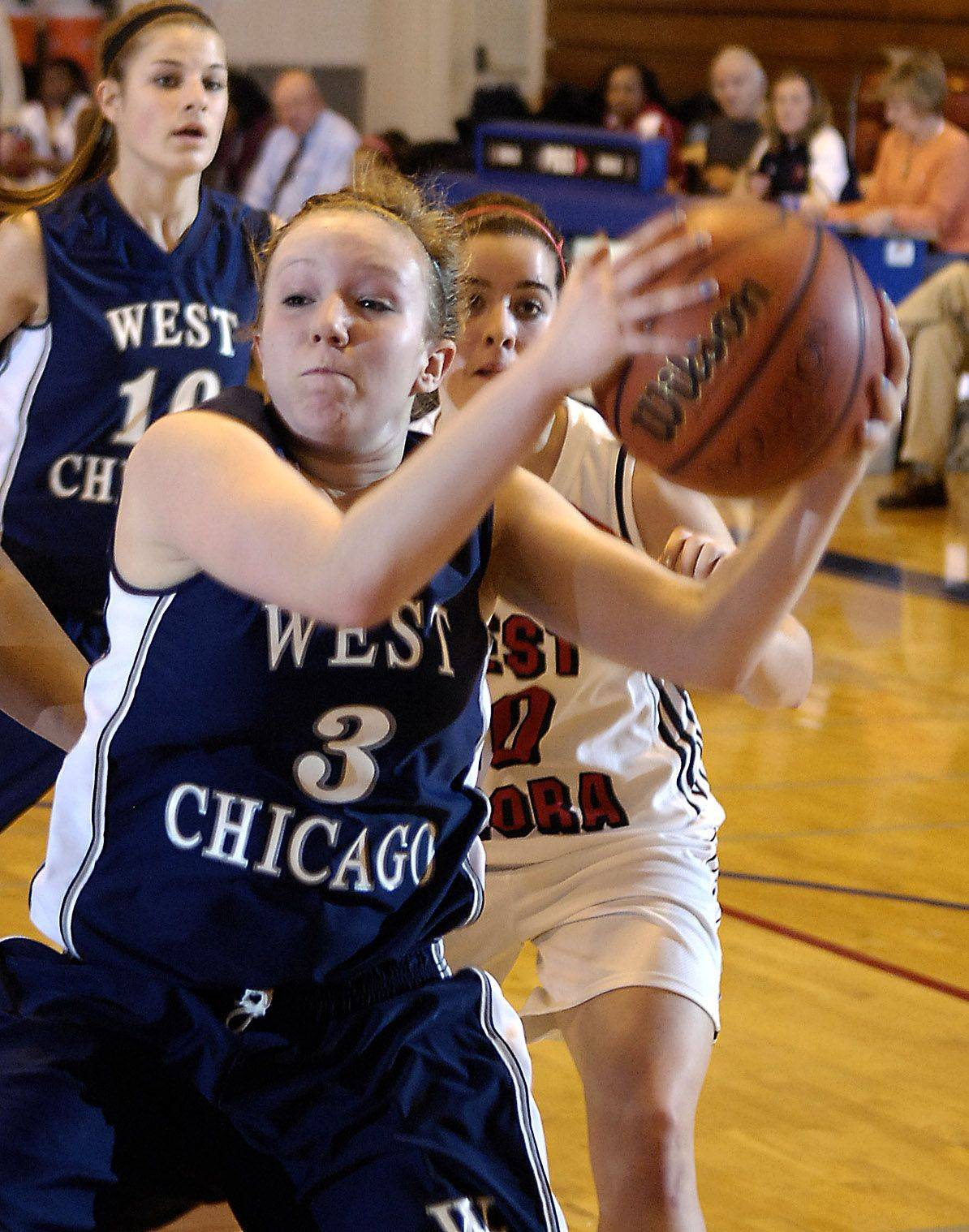 West Chicago's Claire Monroe grabs a rebound in front of West Aurora's Abriya Zeitz during Thursday's game in Aurora.
