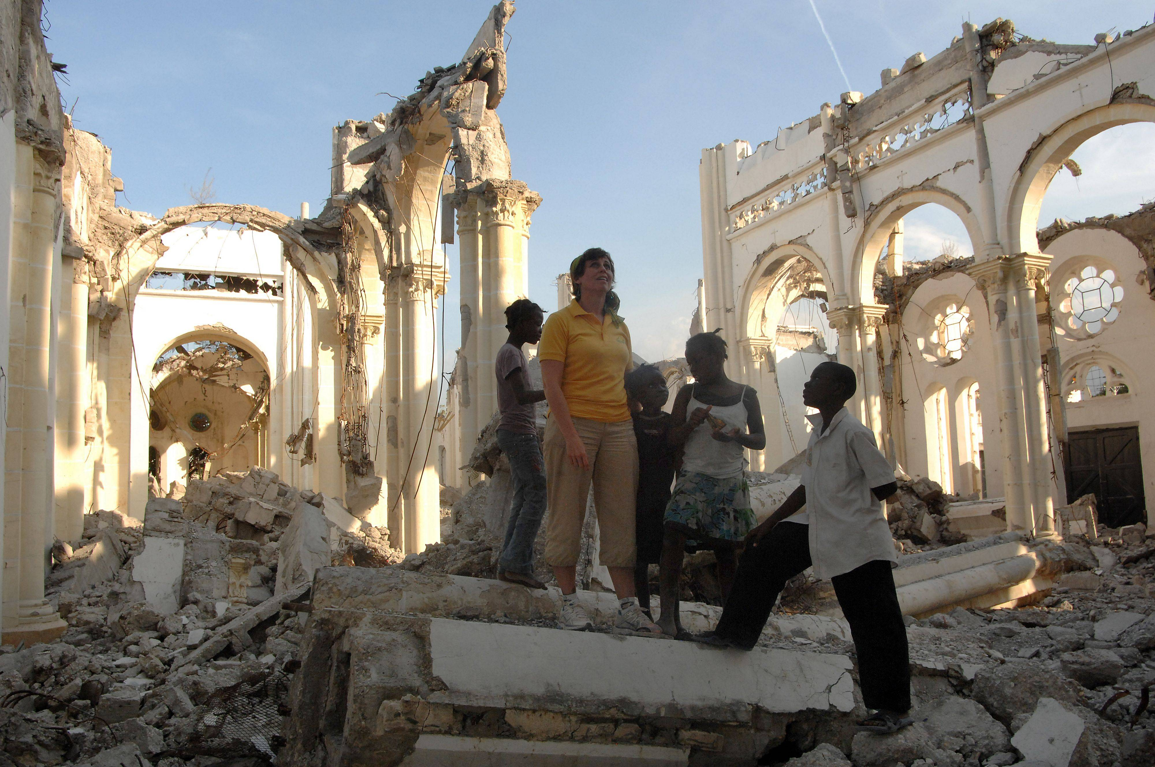 Elk Grove's Lisa Ballantine looks around the remains of the Port-au-Prince Cathedral with street children, who now use the building as a playground.