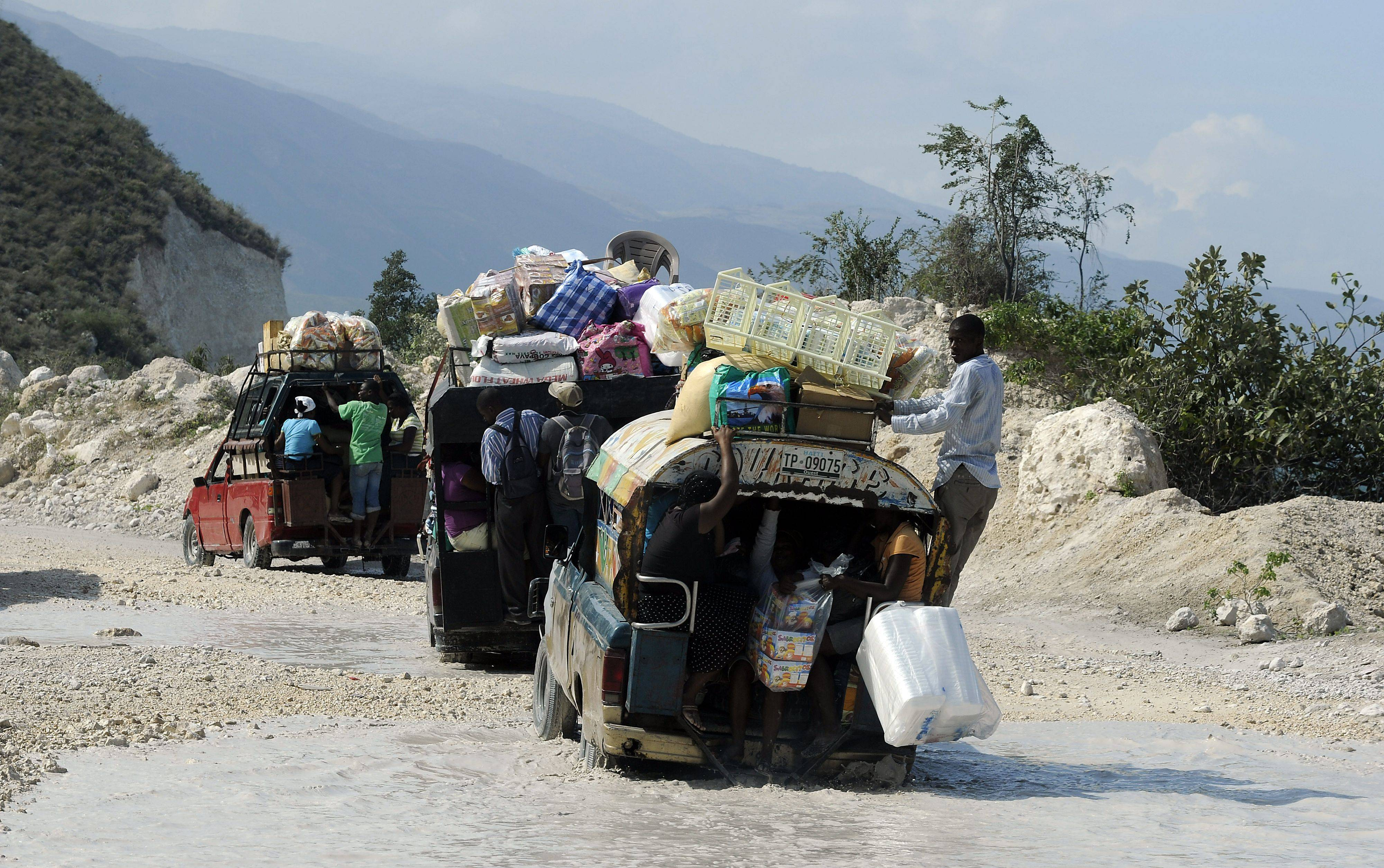 Trucks weighted down with supplies and people cross the border between Haiti and the Dominican Republic .