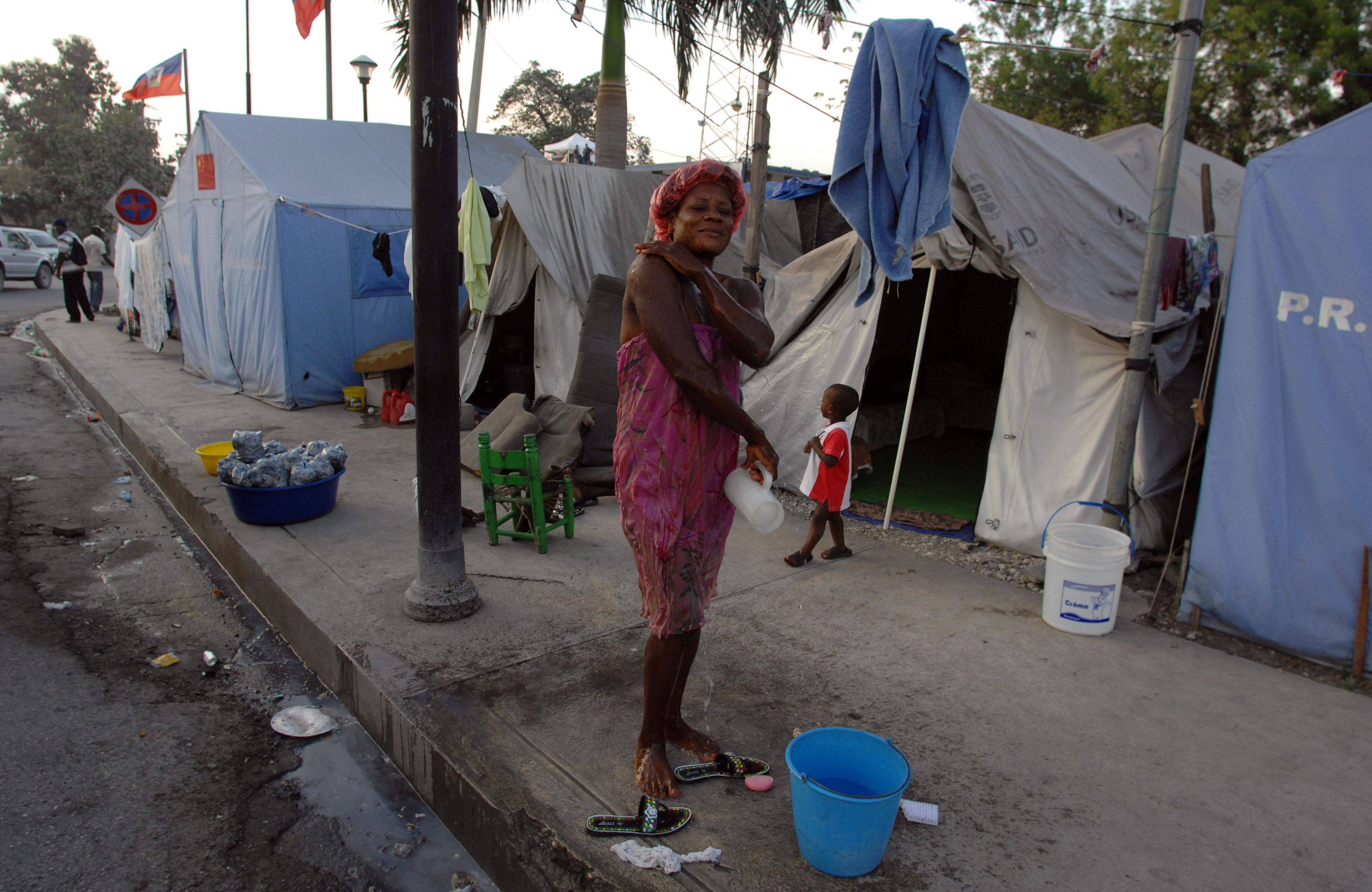 A woman washes herself on the street across from the site of the Haitian Presidential Palace .