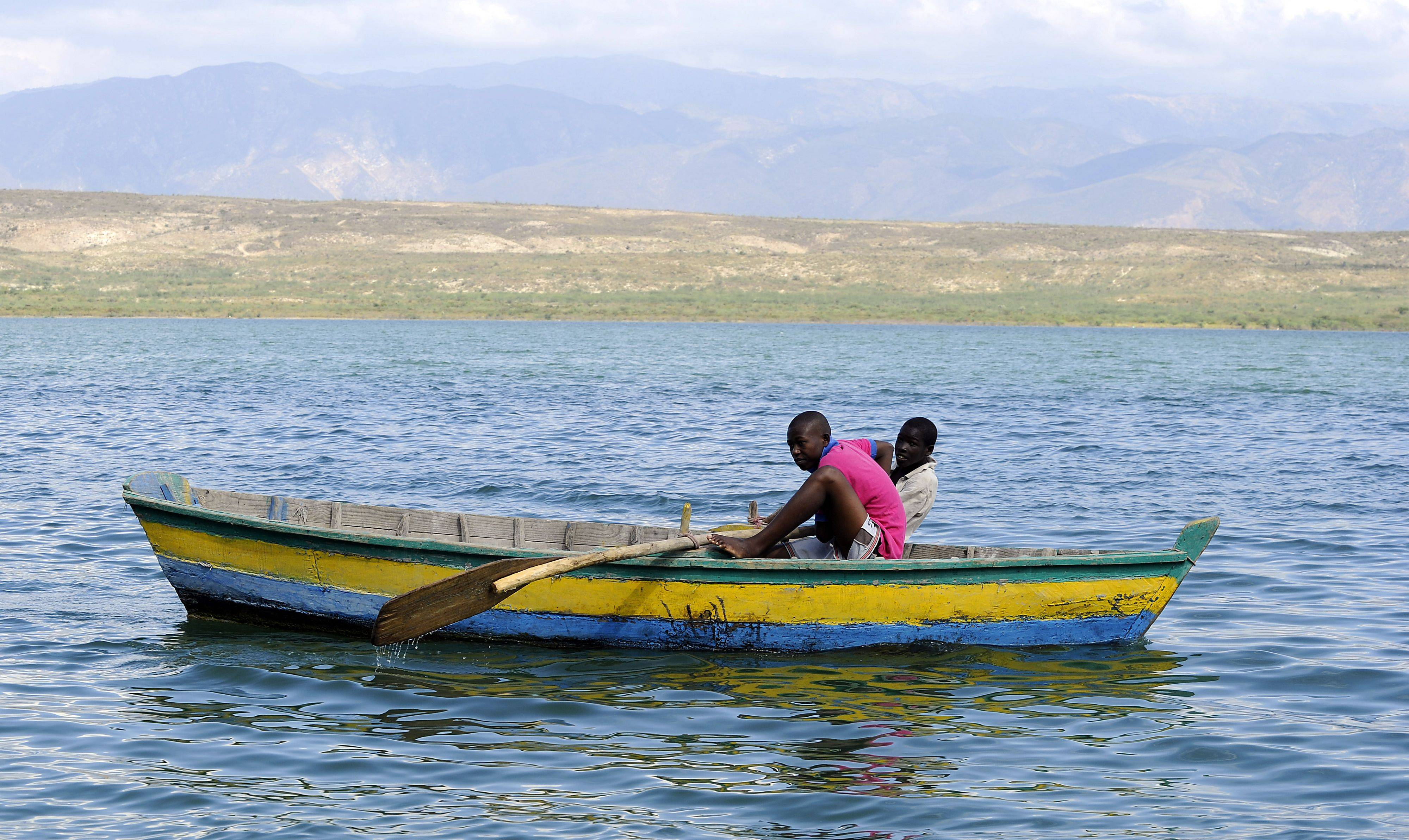 Two boys row near the border of Haiti and the Dominican Republic in a colorful boat.