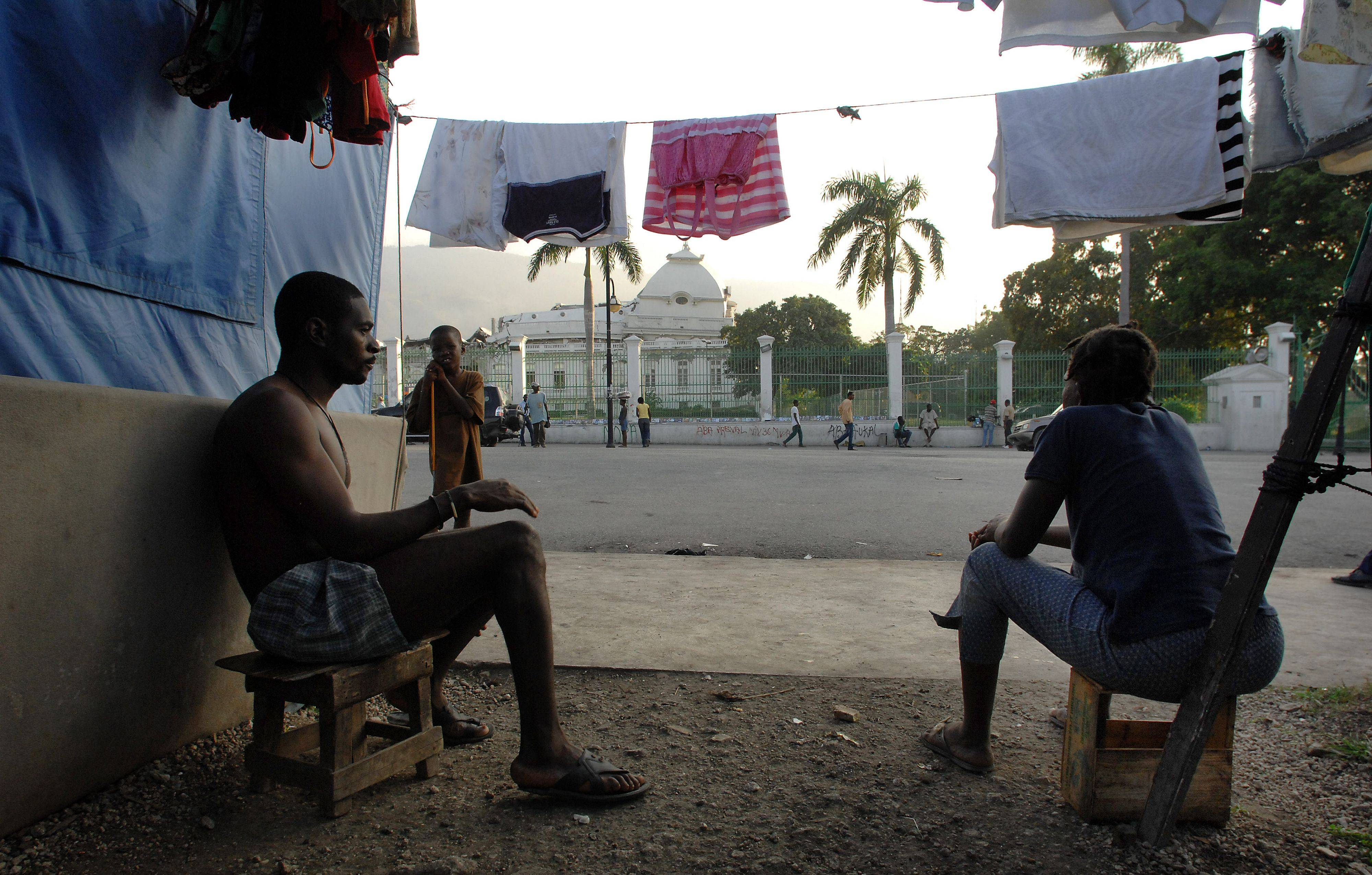 Tent city residents live across the street from the the collapsed Haitian Presidential Palace .