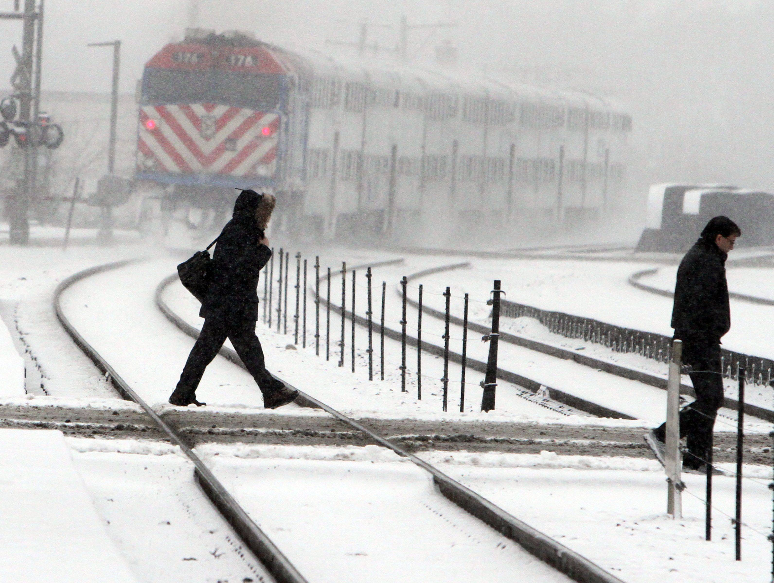 A morning commuter crosses the train tracks at Lee and Miner Streets in Des Plaines as a train pulls in on Tuesday, January 11.