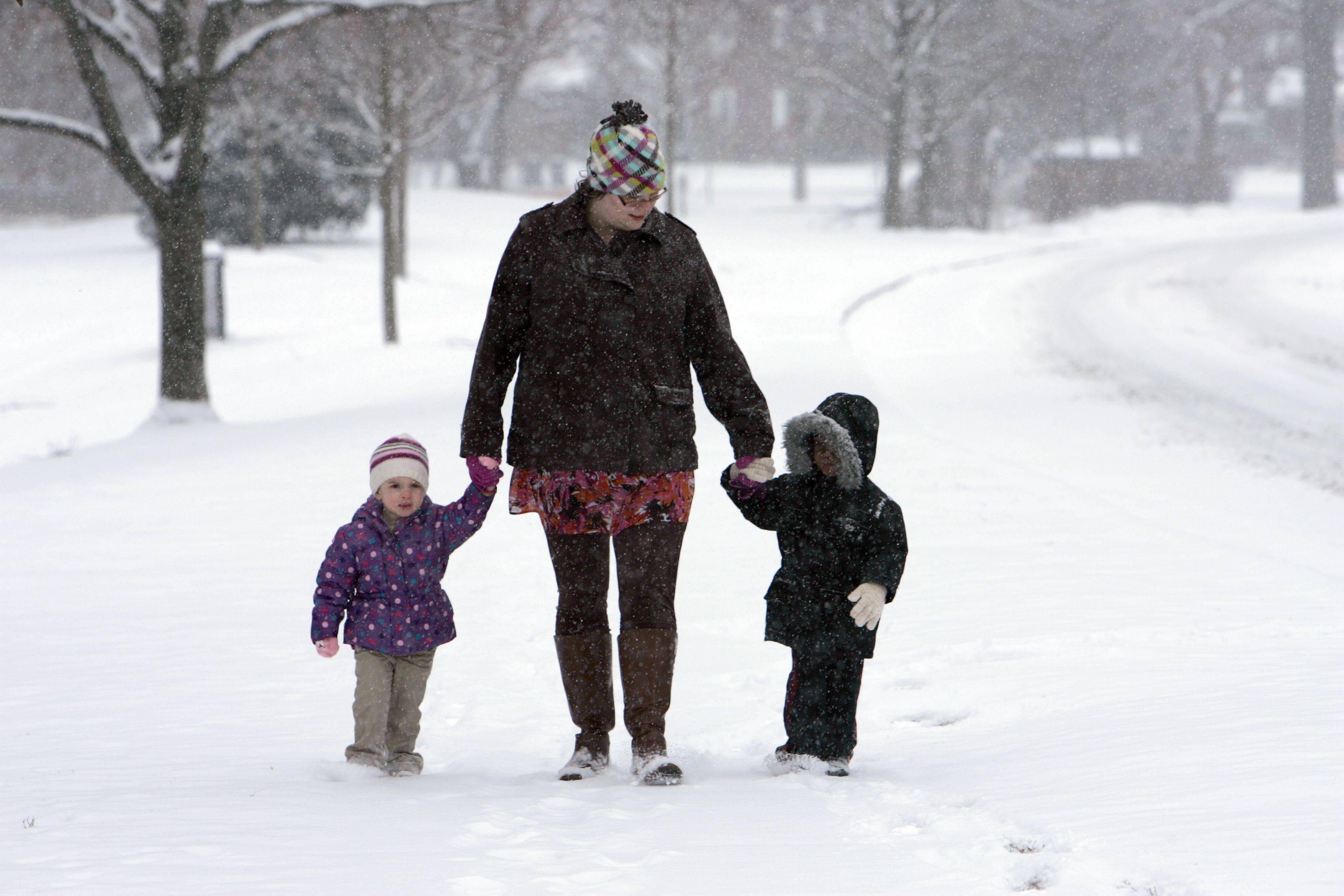 """It's nice to be outside, when it's cold out. I really like it"" says Bethlehem Lutheran Church day care teacher Tina Zastrow, pictured center. Zastrow, Avery Thielen, 2, left and Deondre Stanton, 3 enjoy a stroll in the winter wonderland that was provided on Tuesday. The group was taking their daily walk, this time along Lords Park in Elgin. More flurries are due for Wednesday according to weather.com."