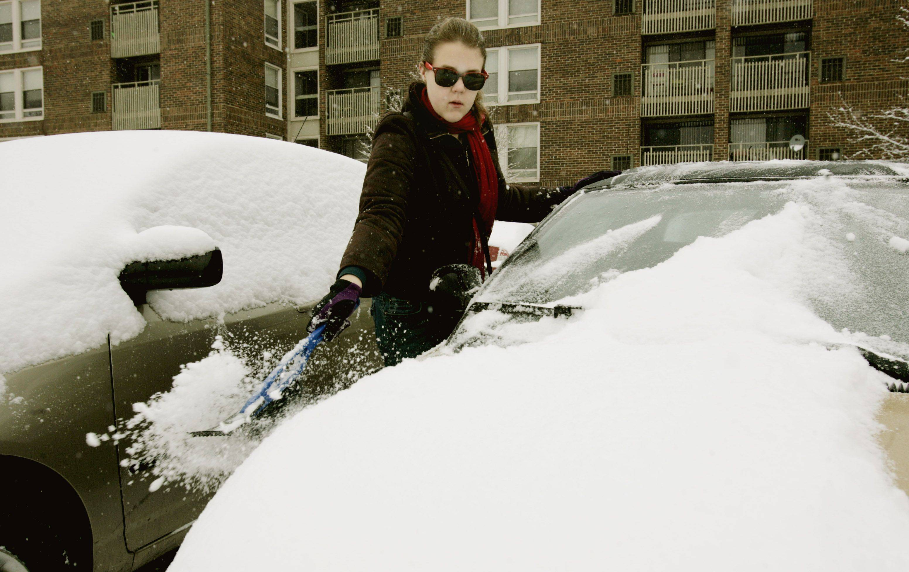 Sandra Kolder, who lives at Arboretum Villages in Lisle, brushes snow off her car Tuesday.