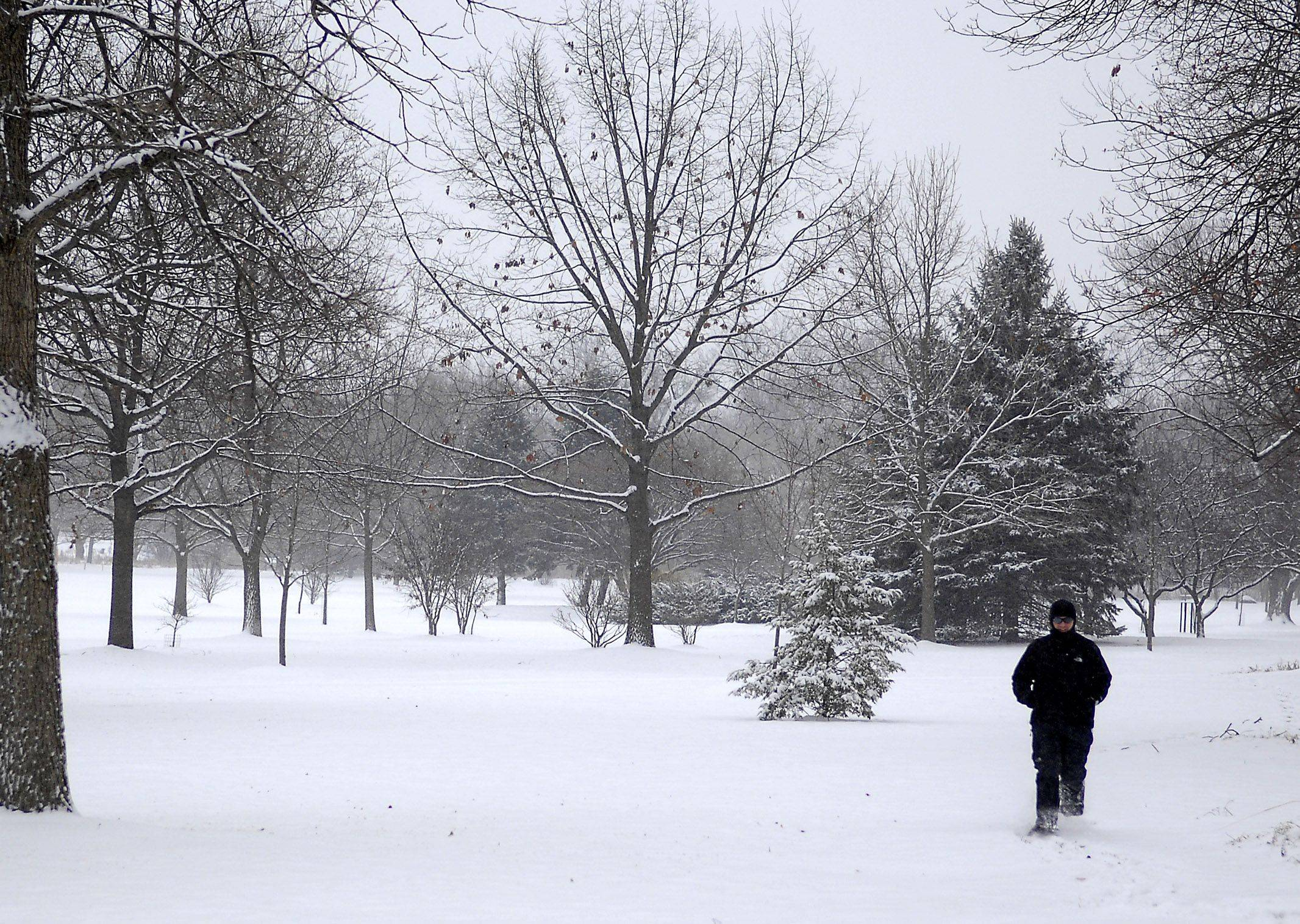 "Andrew Saxer of St. Charles goes for a snowshoe jog through Mt. Saint Mary's park in St. Charles Tuesday afternoon. He said the new-fallen made the conditions ""just right."""