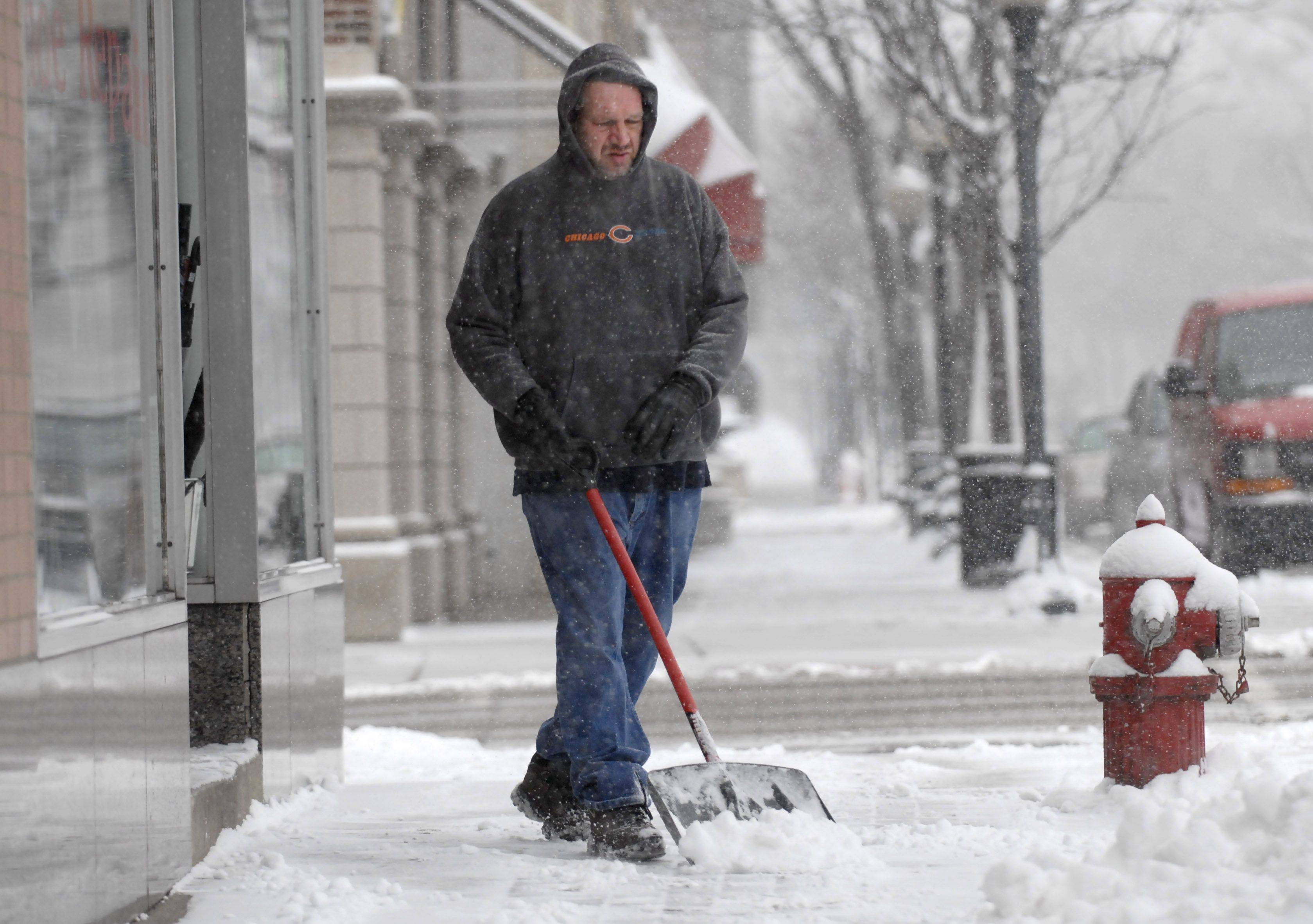 Kenny Callahan, owner of First Arlington Barber Shop keeps his sidewalk clear on Campbell Street after a few inches of fluffy snow fell Tuesday morning in Arlington Heights.