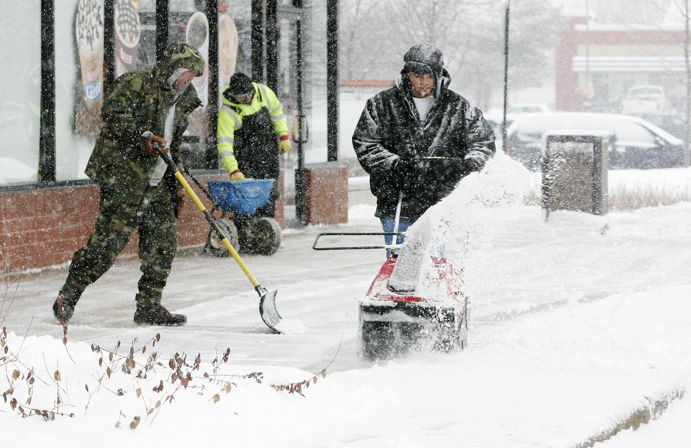 Gilbert R. Boucher II/gboucher@dailyherald.comAlex Garcia uses a snow blower to clear the sidewalks with other employees from Building Maintenance Systems Tuesday at Hawthorn Hills Square in Vernon Hills as snow fell in Lake County.