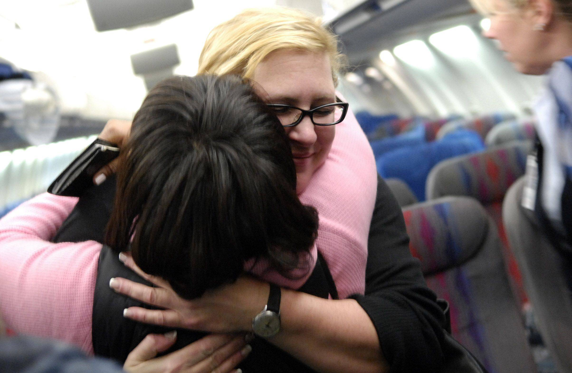 Purser Supervisor Carol Bartacchi hugs Managing Director of Corporate Social Investment Sonya Jackson after their return from United Airlines first relief flight to Haiti and back.