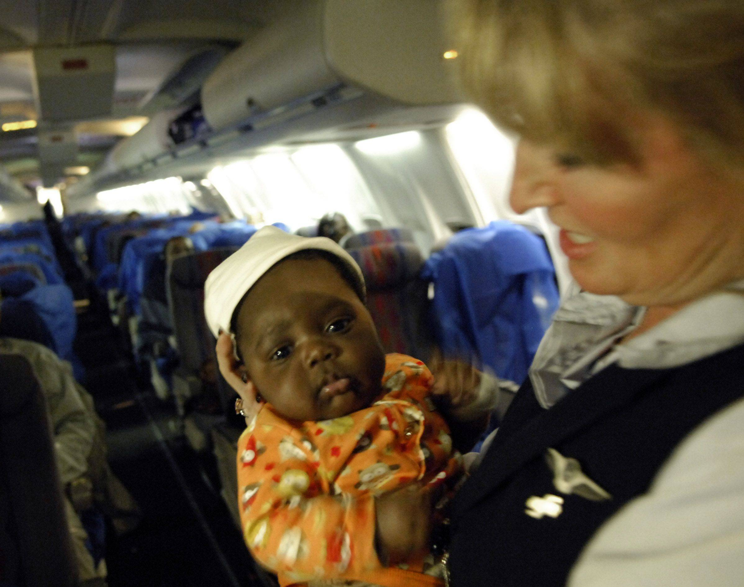 Flight attendant Corrine Hart-Cooley helps spell a mother by taking 2-month old Jamesly Paul for a walk around the cabin during United's first relief flight to and from Port Au Prince Haiti.